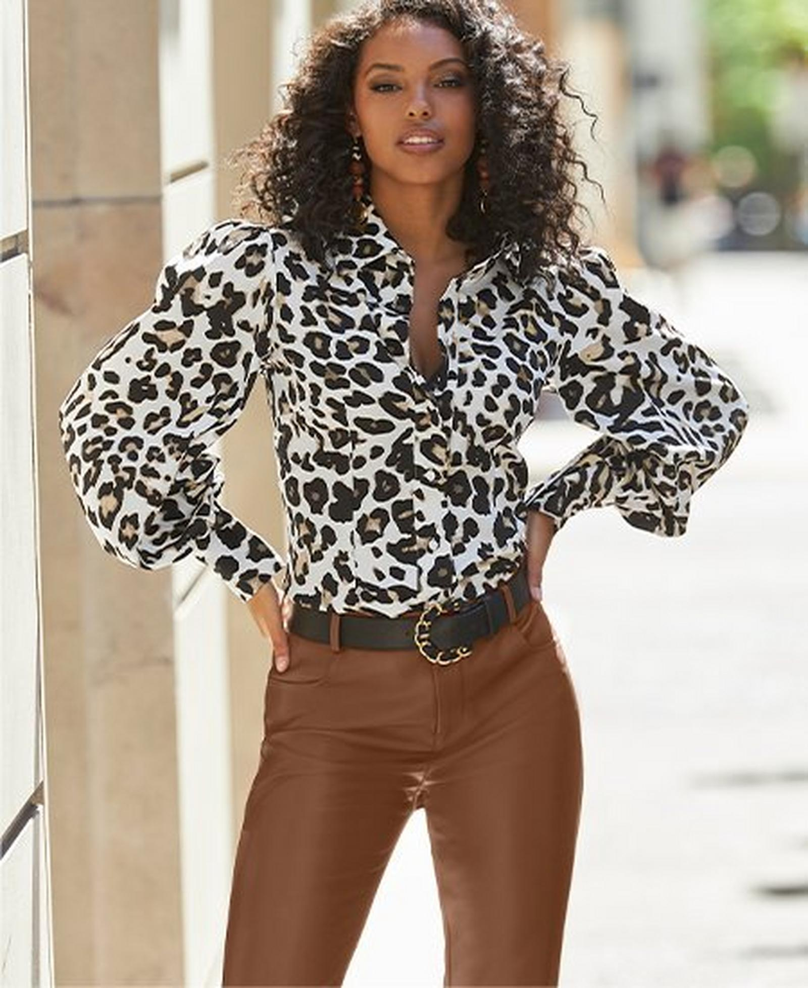 model wearing a leopard print drama sleeve button-down top, black belt, and brown faux-leather pants.