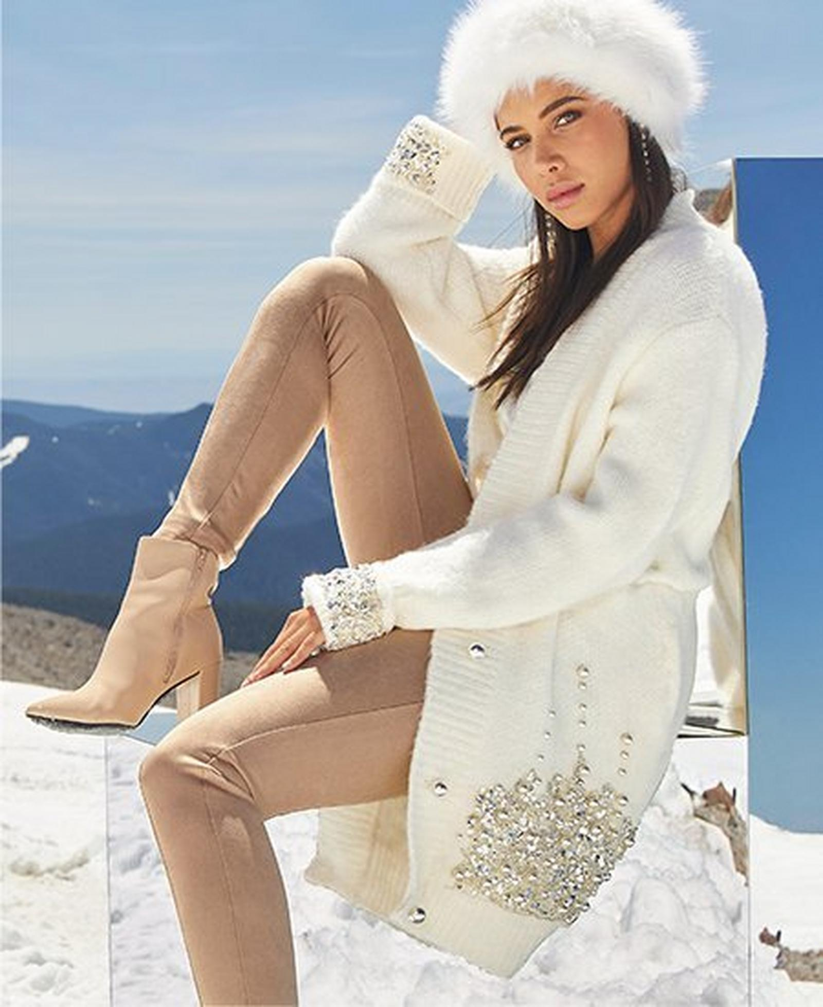 model wearing a white rhinestone embellished cardigan, tan faux-suede leggings, tan leather booties, and a white faux-fur hat.
