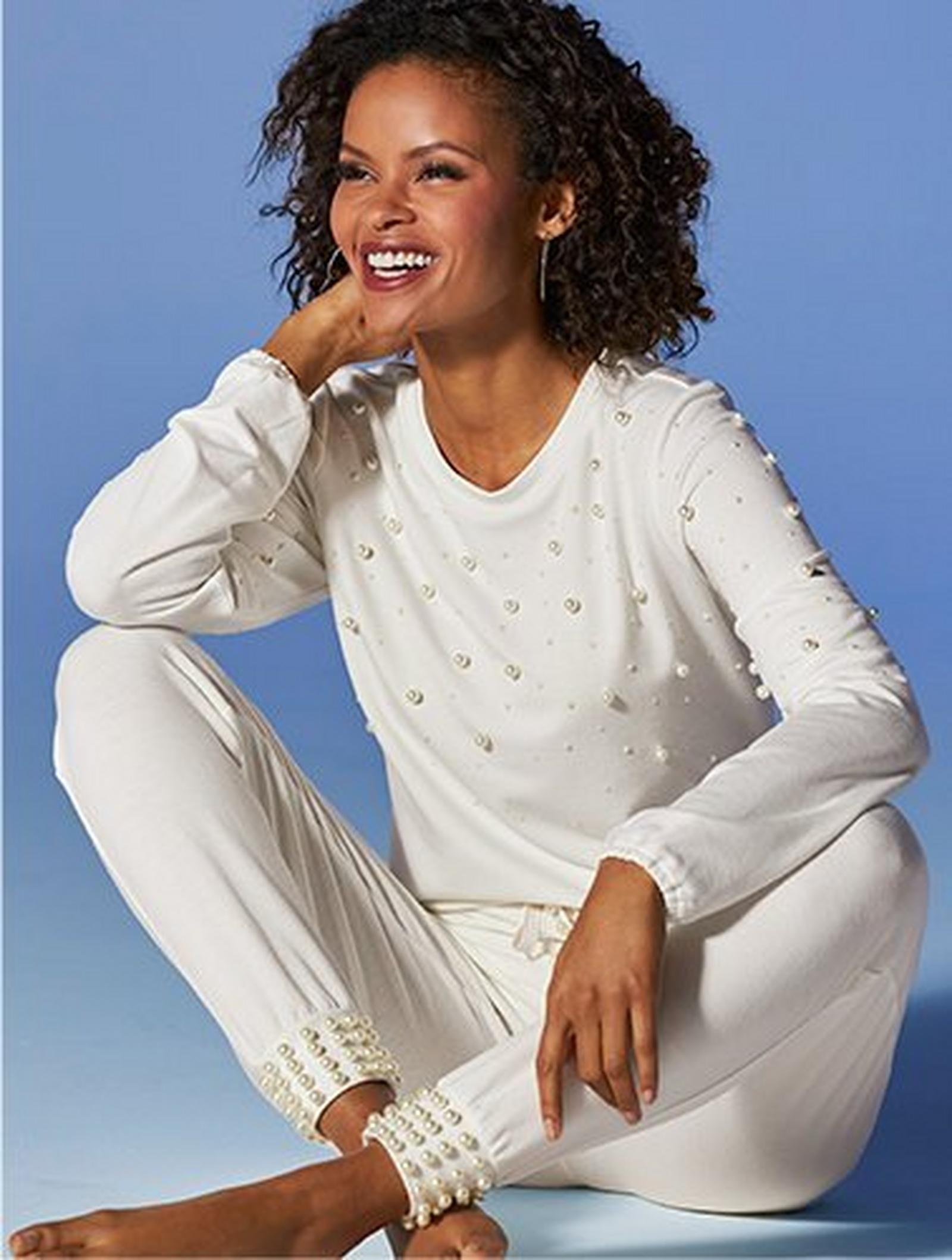 model wearing a white pearl embellished sweater and matching joggers.