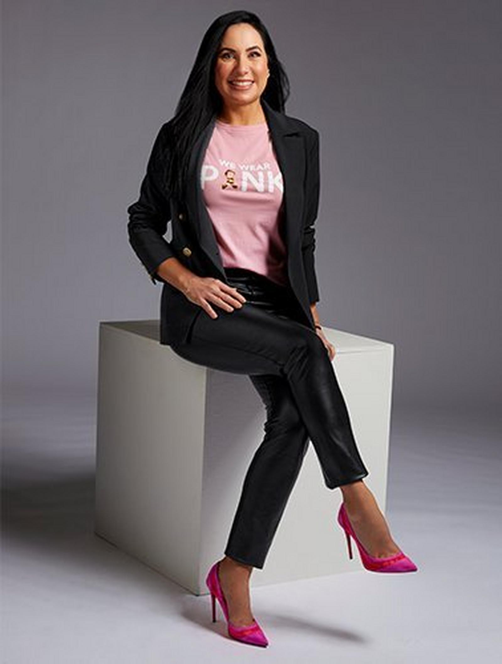 model wearing a black cardigan, black faux-leather pants, pink pumps, and a pink breast cancer awareness themed shirt that says