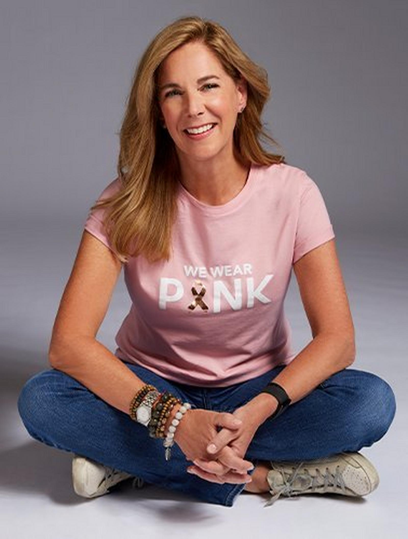 model wearing a pink breast cancer awareness themed shirt that says