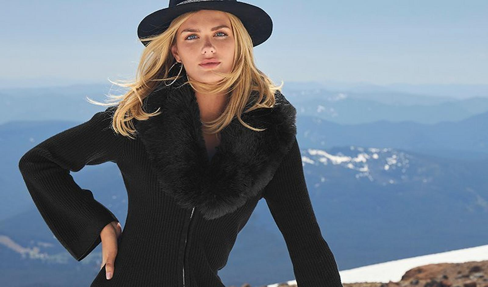 model wearing a black ribbed cardigan with a black faux-fur collar and a black hat.