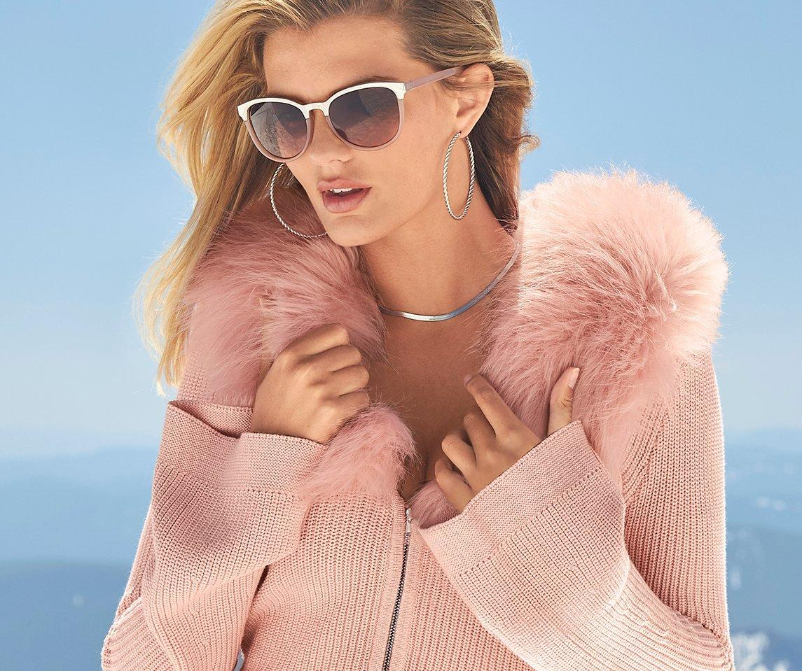 model wearing a light pink ribbed cardigan with a faux-fur collar.
