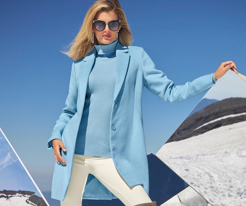 model wearing a light blue blazer, light blue ribbed turtleneck sweater, and off-white leggings.