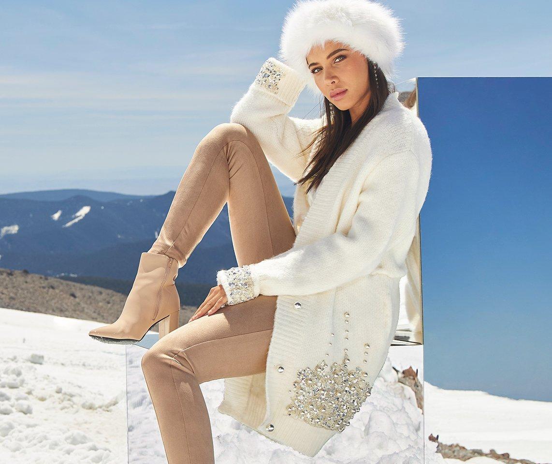 model wearing a white rhinestone embellished plush cardigan, white faux fur hat, tan faux-suede leggings, and tan heeled booties.