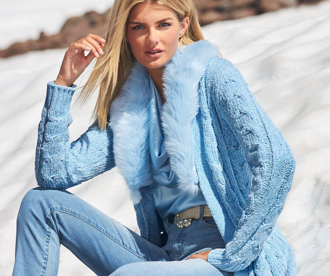 model wearing a light blue faux-fur long chenille sweater duster, light blue cowl neck top, and light wash jeans.