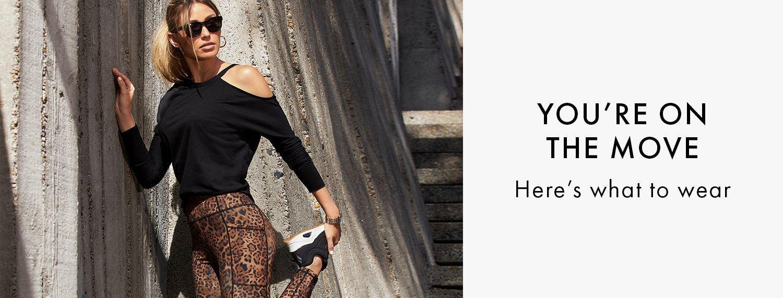 model wearing a black one-shoulder long-sleeve tee and brown animal print leggings.