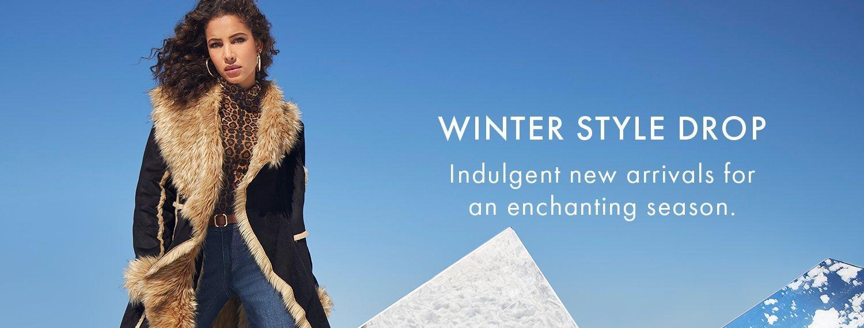 model wearing a black cascading long coat with tan faux fur lining.