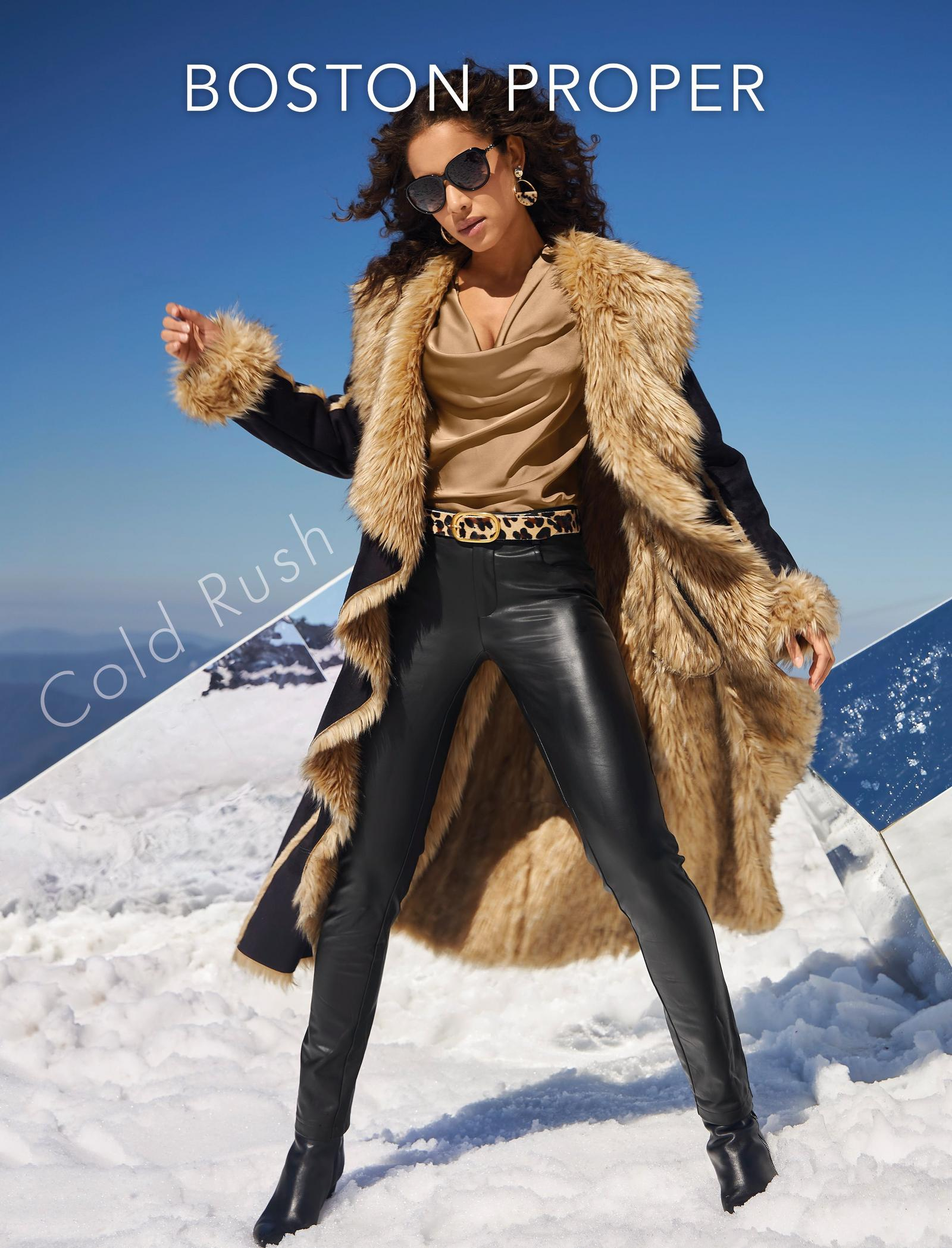 model wearing a black cascading long coat with tan faux-fur, tan cowl neck top, animal print belt, black faux-leather pants, and black booties.