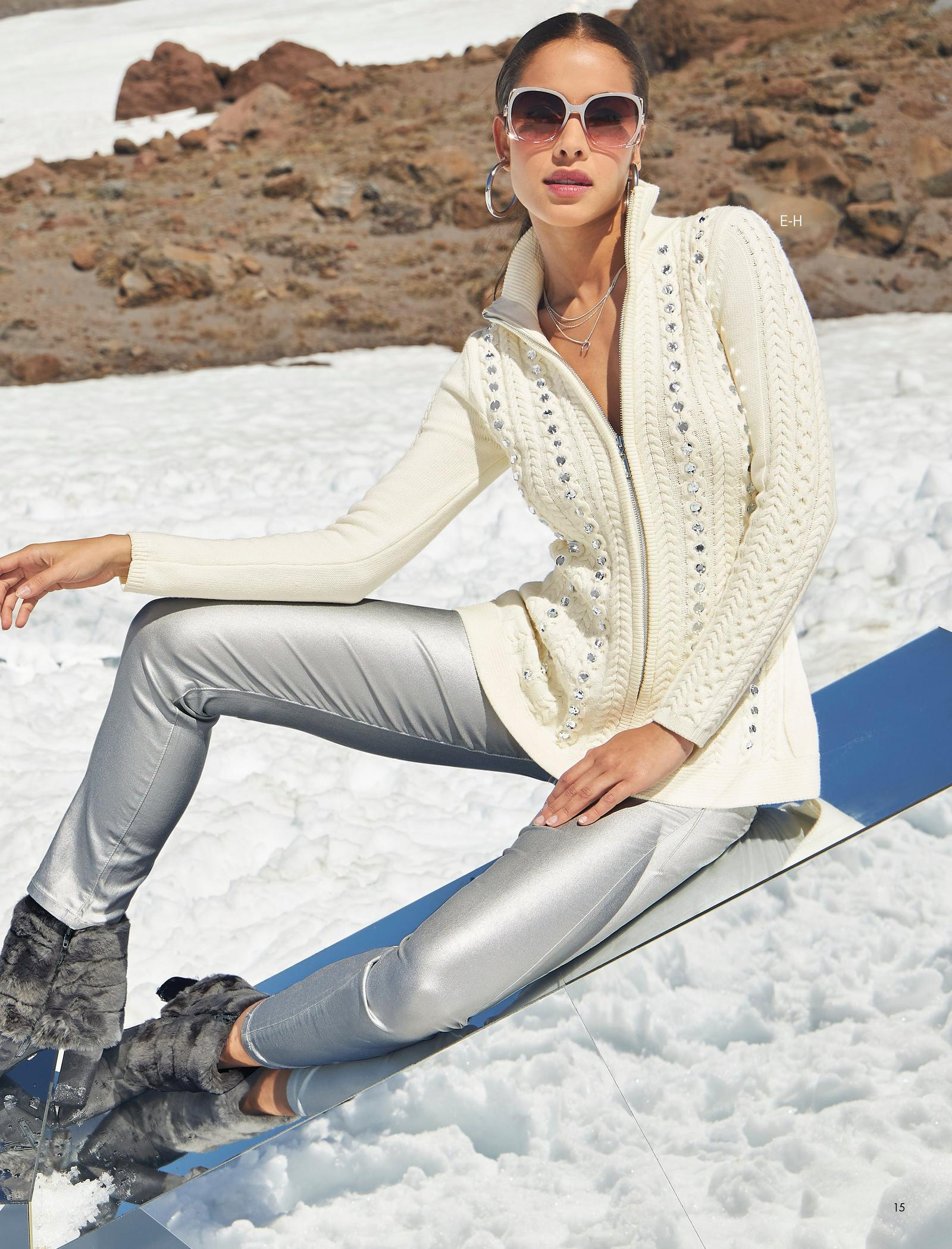 model wearing a white cable-knit full-zip rhinestone embellished cardigan, silver coated jeans, and faux-fur trim ankle booties.