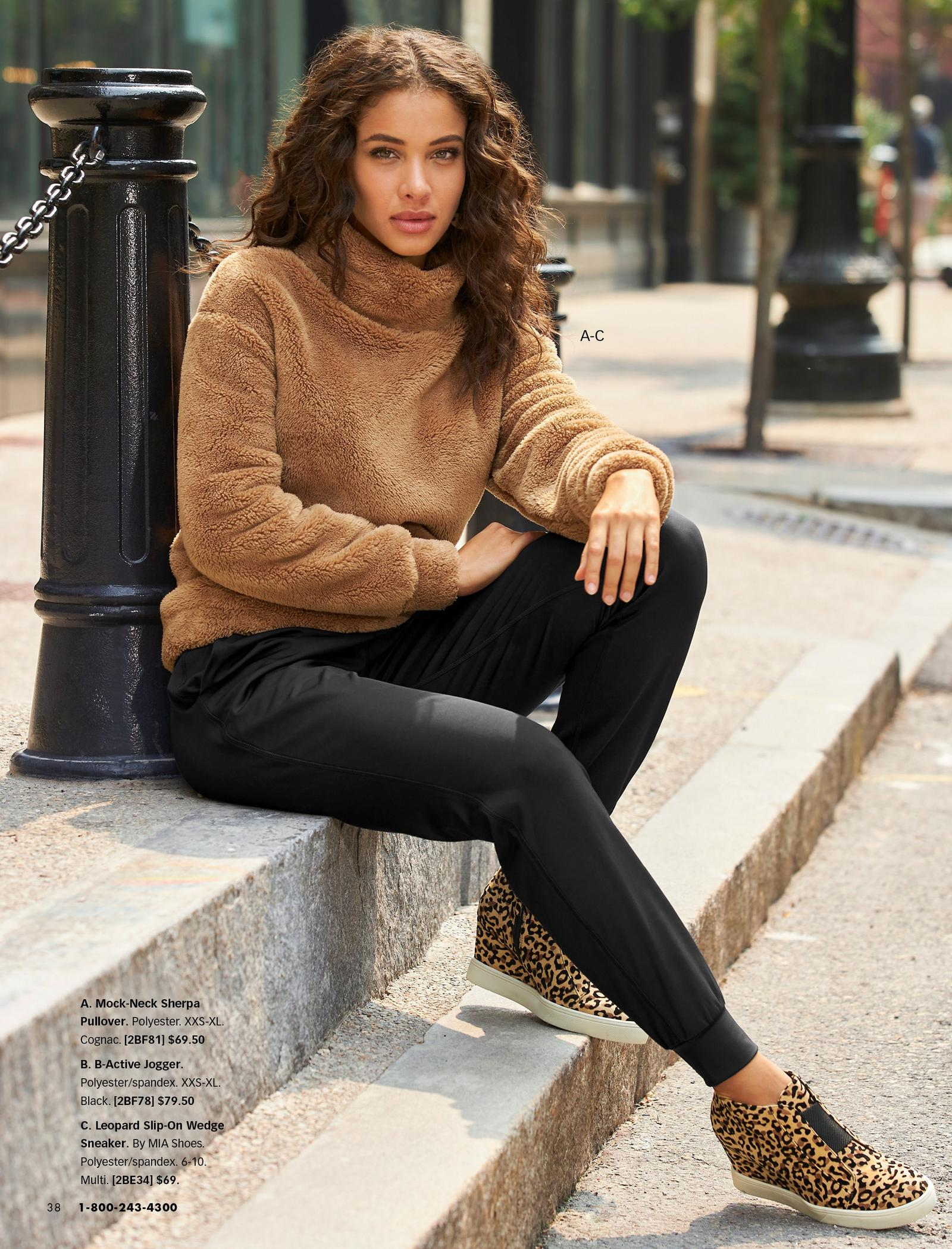 model wearing a tan mock-neck sherpa pullover, black joggers, and leopard slip-on wedge sneakers.