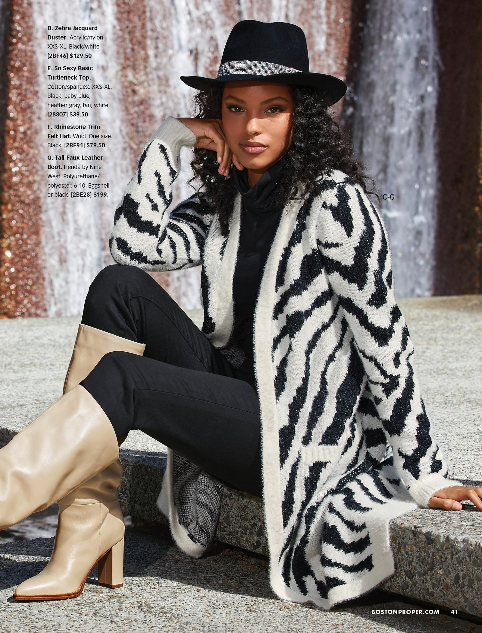 model wearing a black and white zebra duster, black turtleneck top, black jeans, black rhinestone trim felt hat, and tan faux-leather under-the-knee boots.