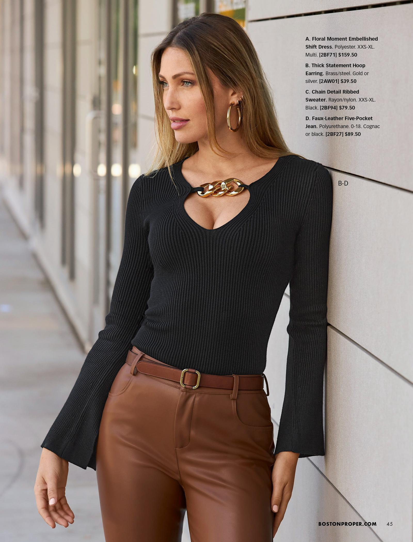 model wearing a black ribbed chain detail keyhole sweater, brown belt, gold hoop earrings, and brown faux-leather jeans.
