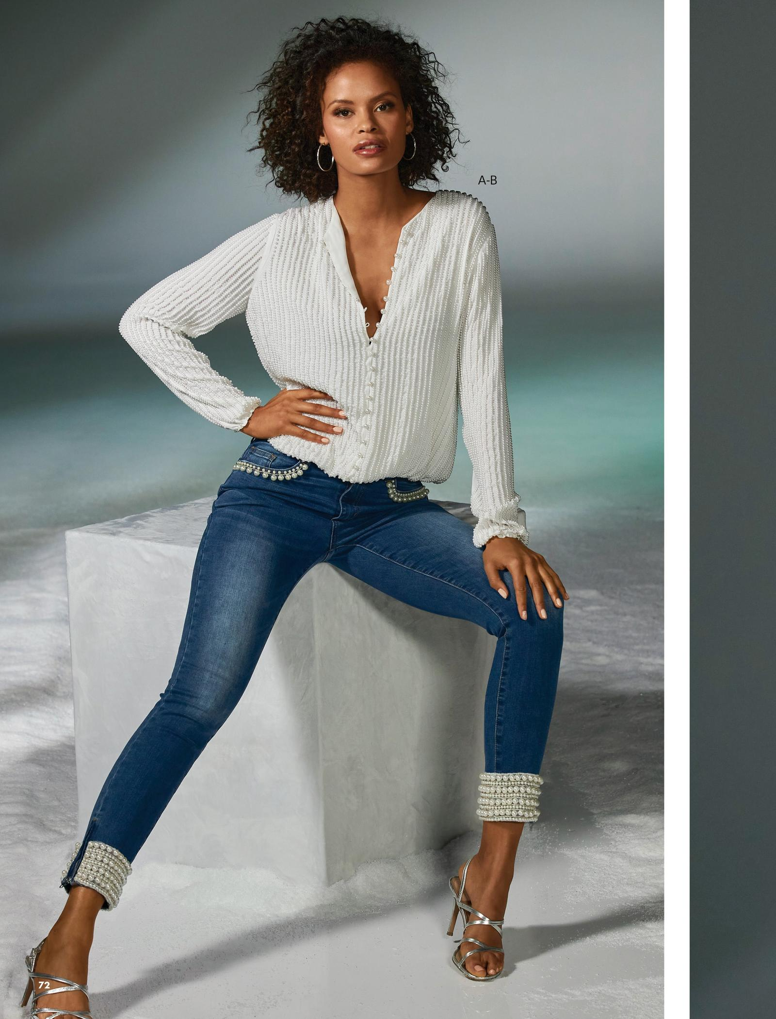 model wearing a white pearl embellished long-sleeve blouse, pearl embellished jeans, silver strappy heels, and silver hoop earrings.