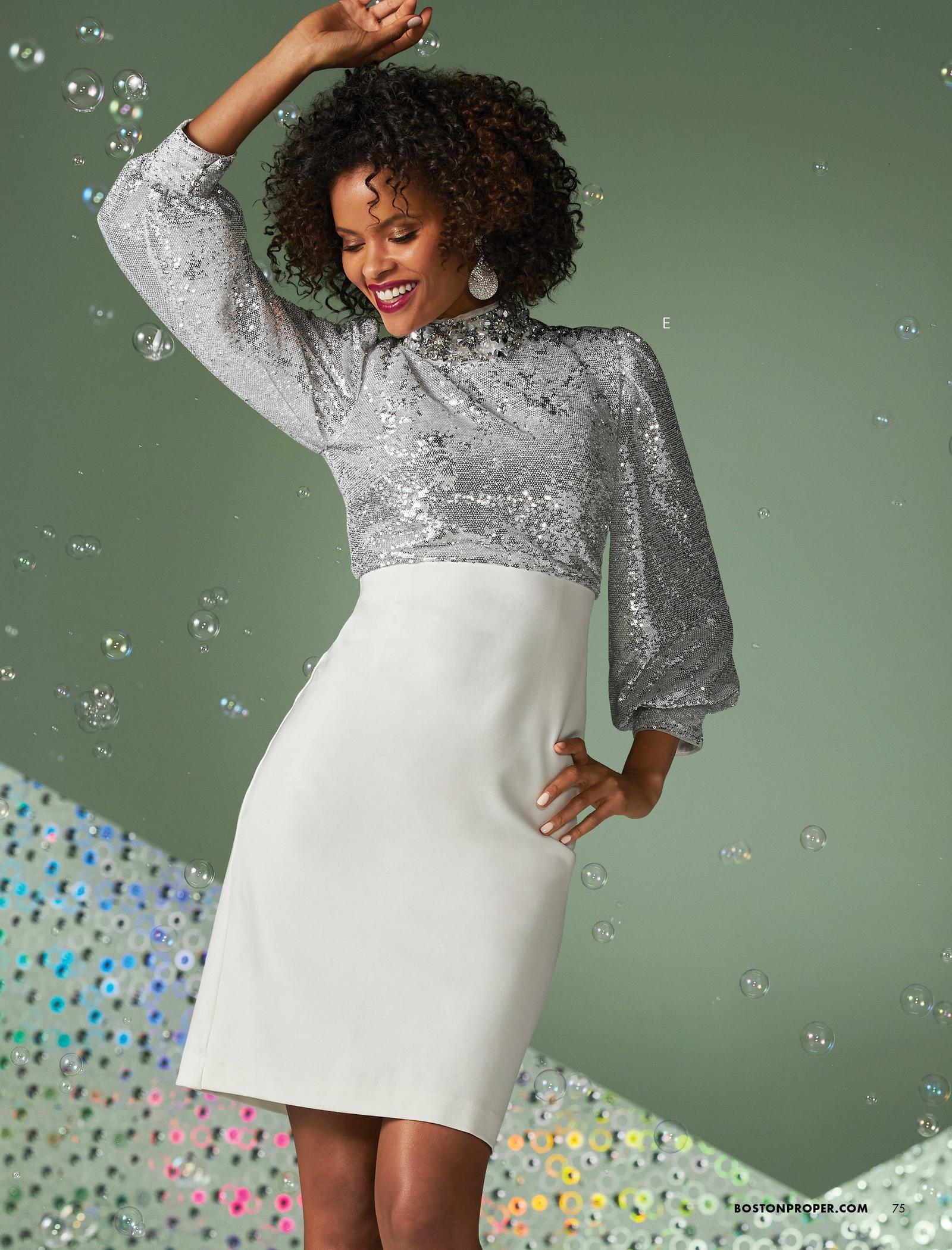 model wearing a silver sequin long-sleeve dress with a white skirted bottom.