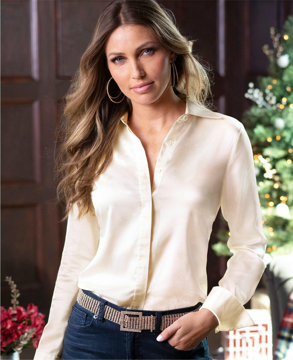 model wearing a cream colored button-up long sleeve blouse.