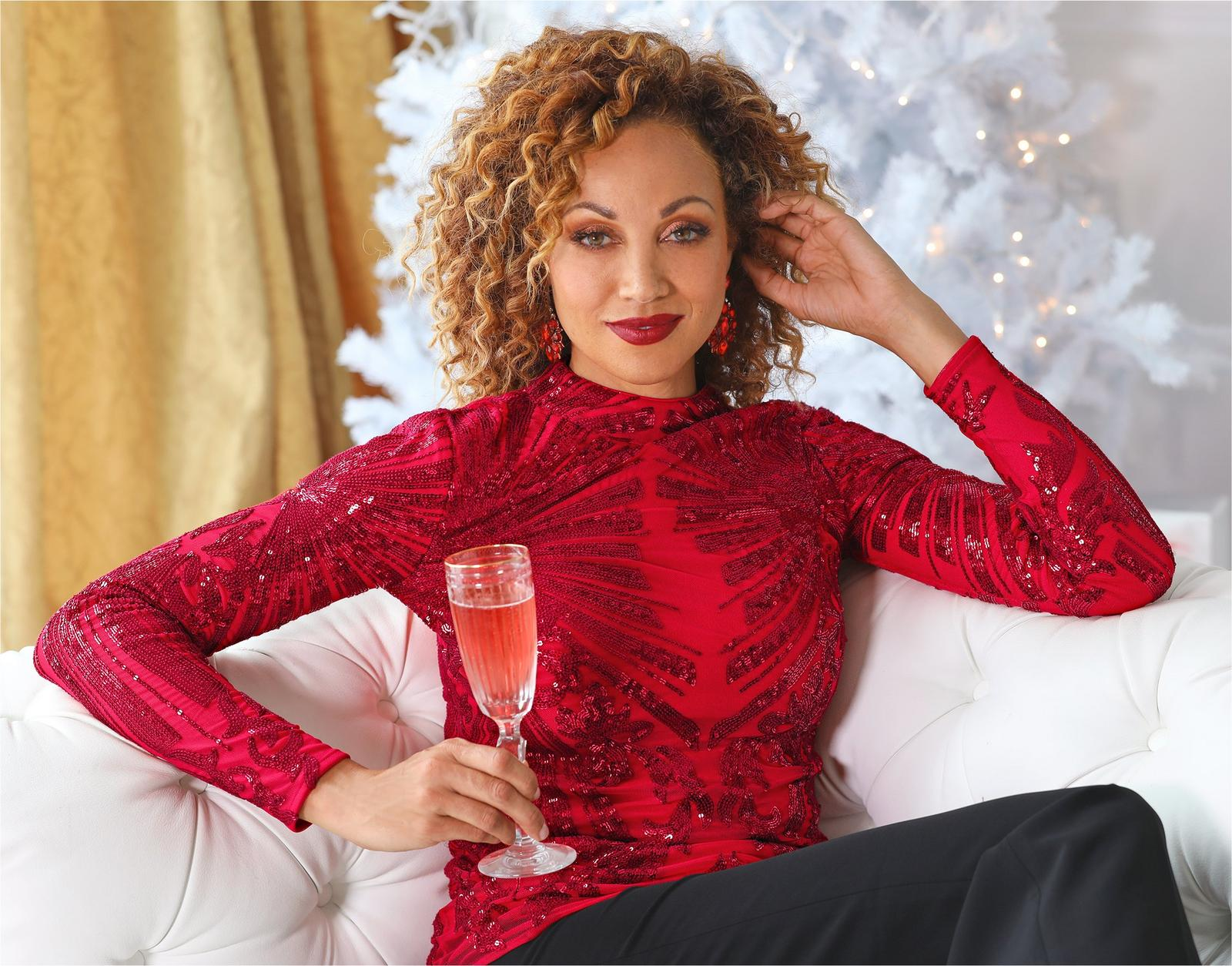 model wearing red sequin mock neck long-sleeve top with black pants and holding a glass of champagne.