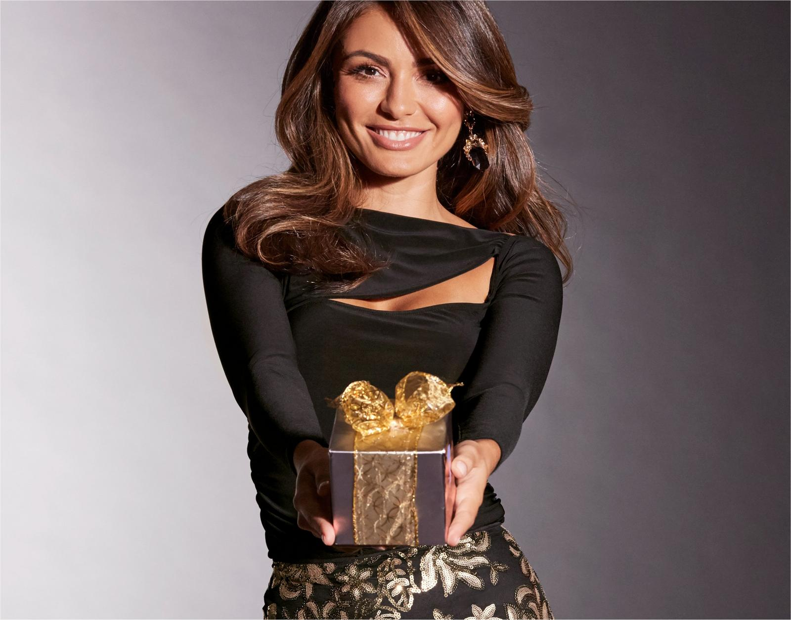 model wearing black cut out top with gold and black skirt while holding a gift.