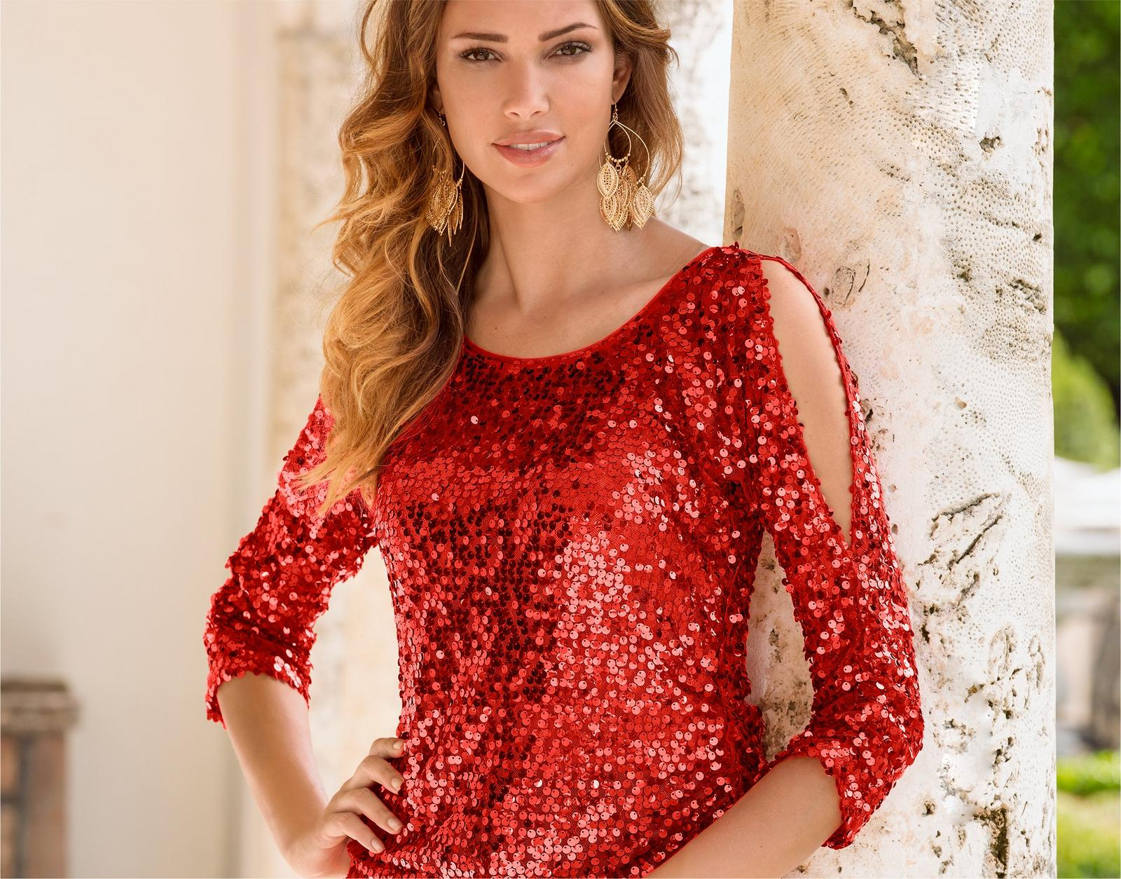 model wearing red sequin cold shoulder top with gold earrings.