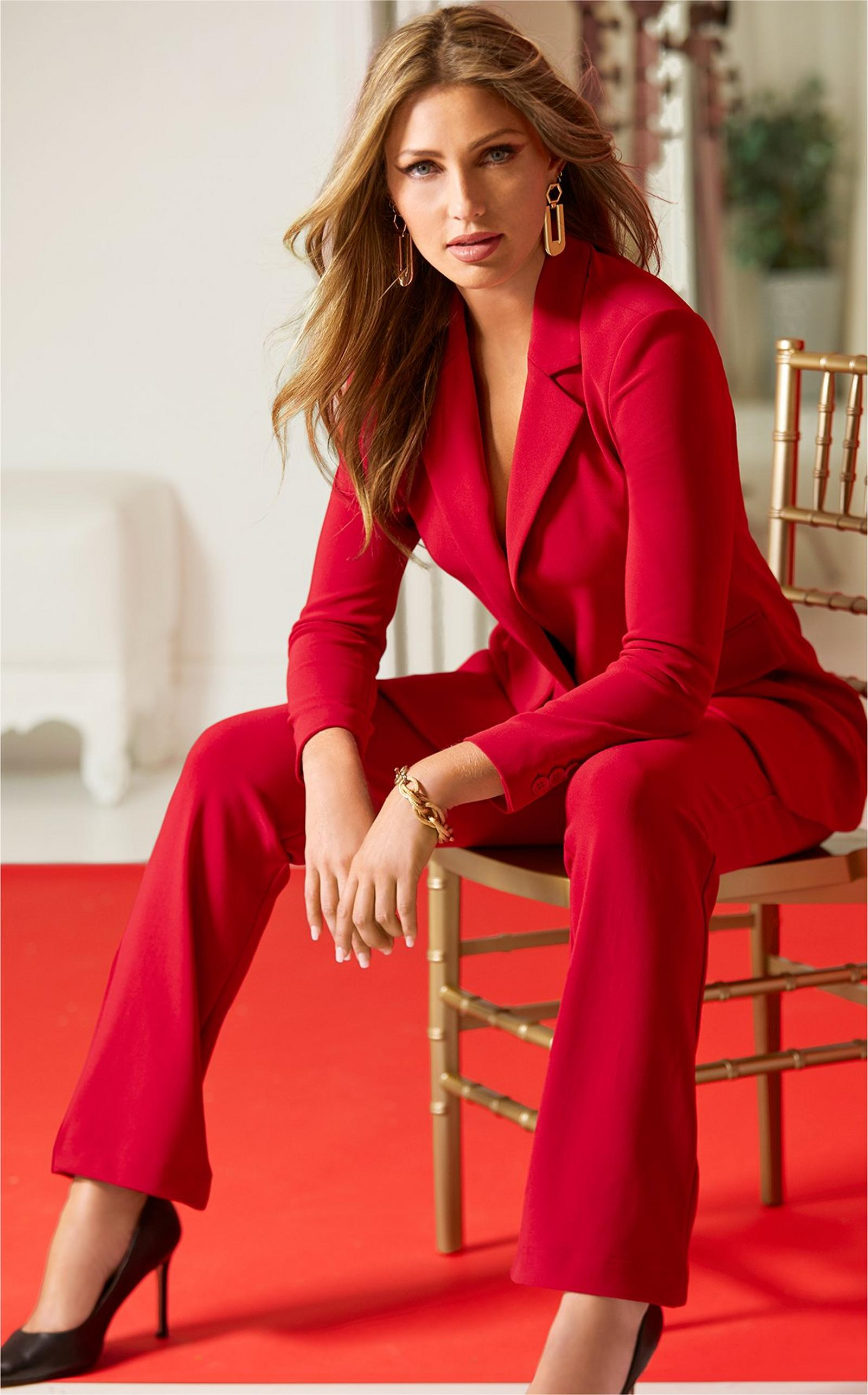 model sitting in a wooden chair wearing a red blazer and red travel pants with black pumps.