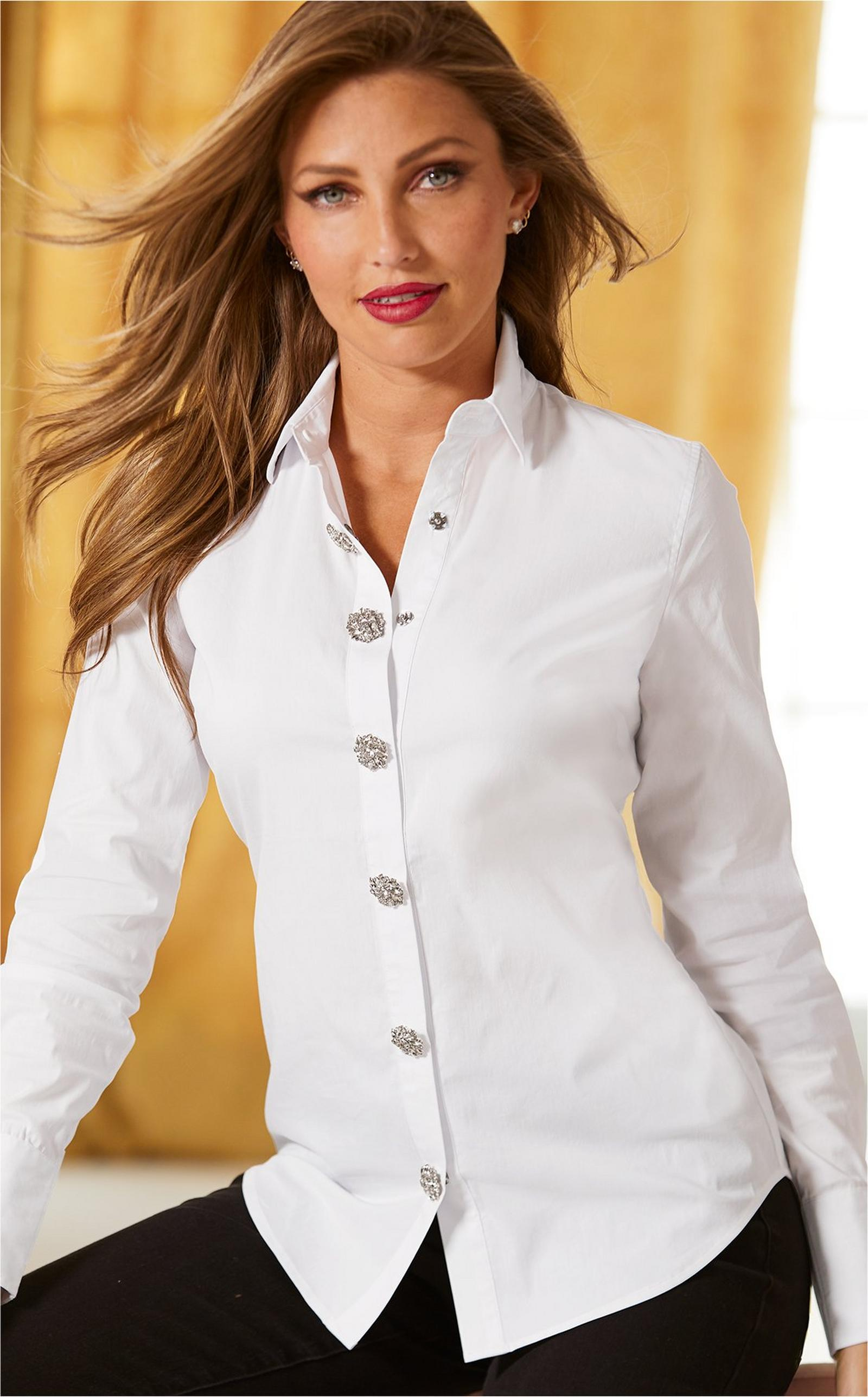 model wearing white embellished button up top with black pants.