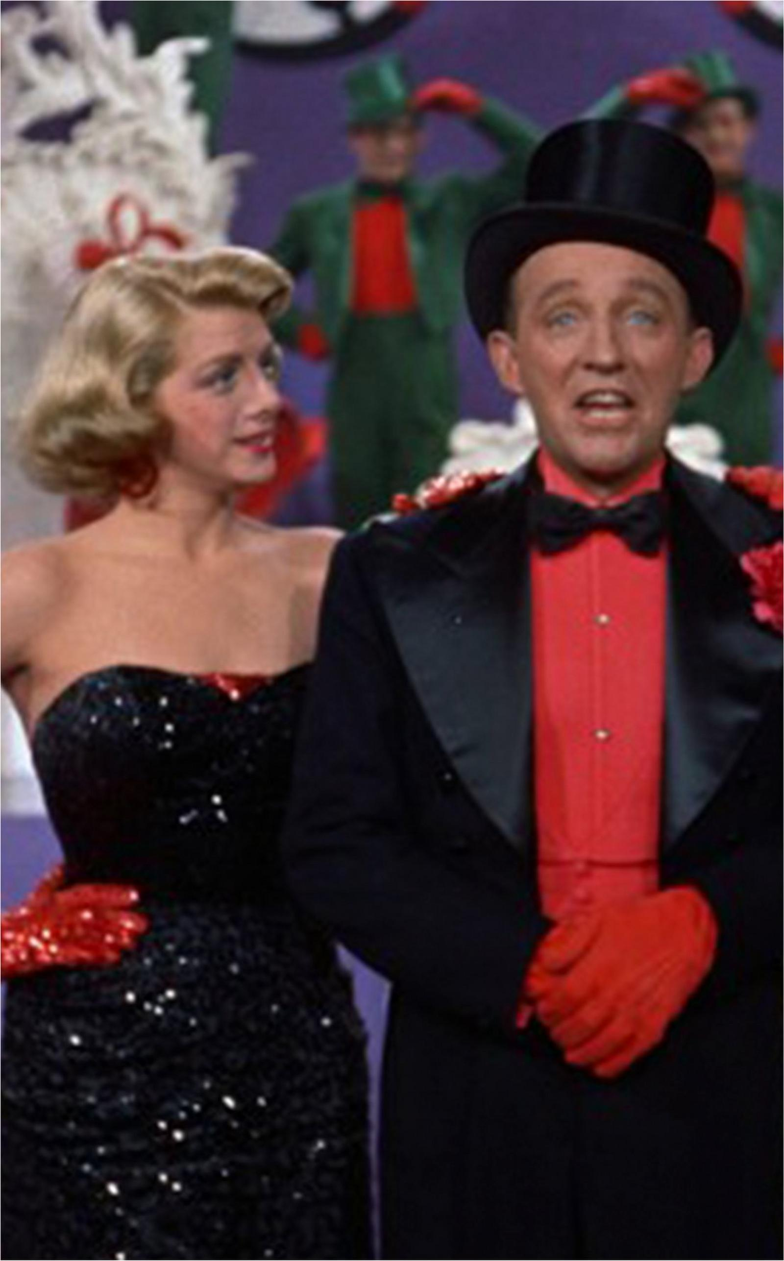 betty haynes from white christmas wearing a sequin black strapless dress standing next to a man in a festive outfit.