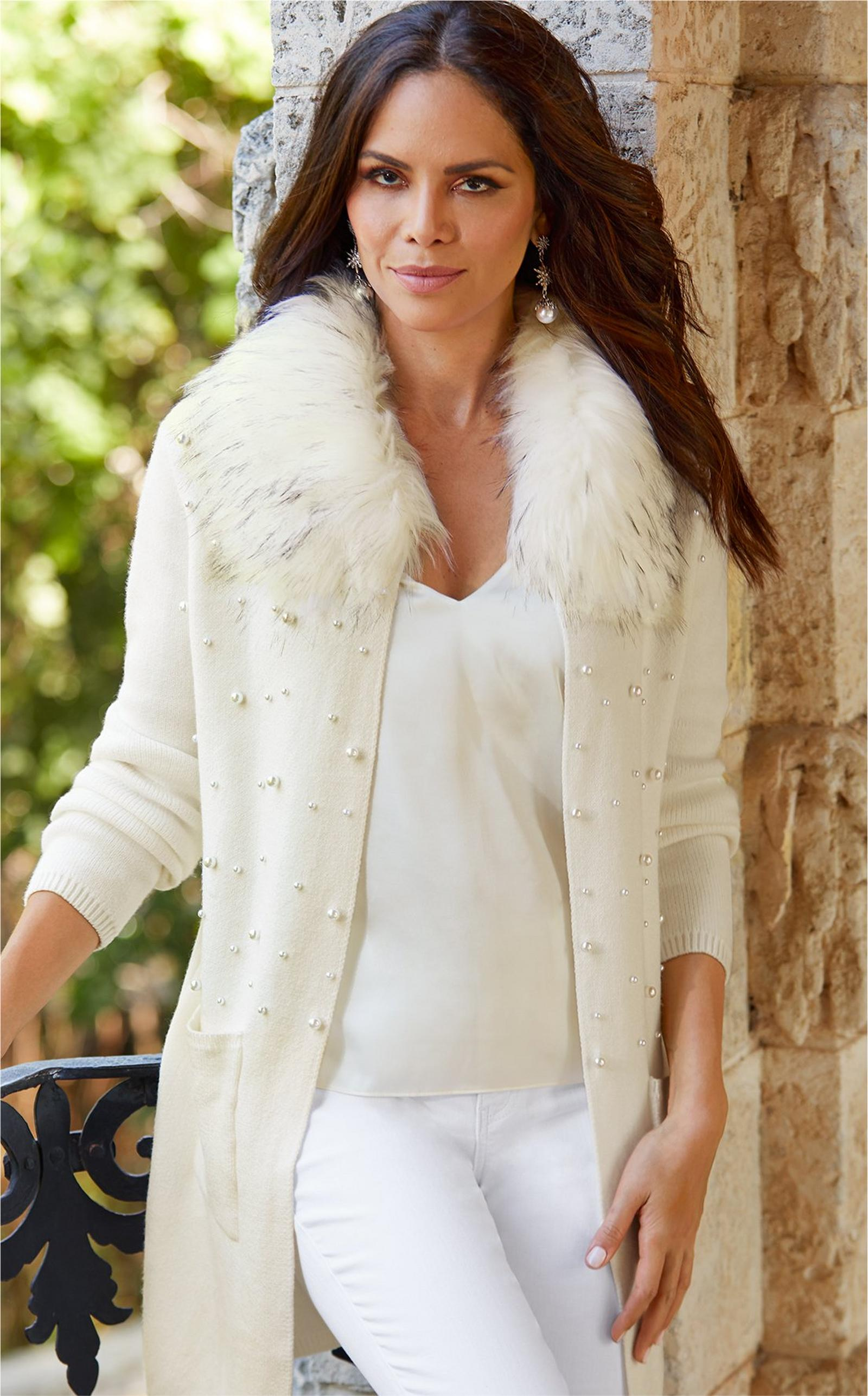 model wearing cream colored faux fur embellished cardigan over cream tank top and white jeans.