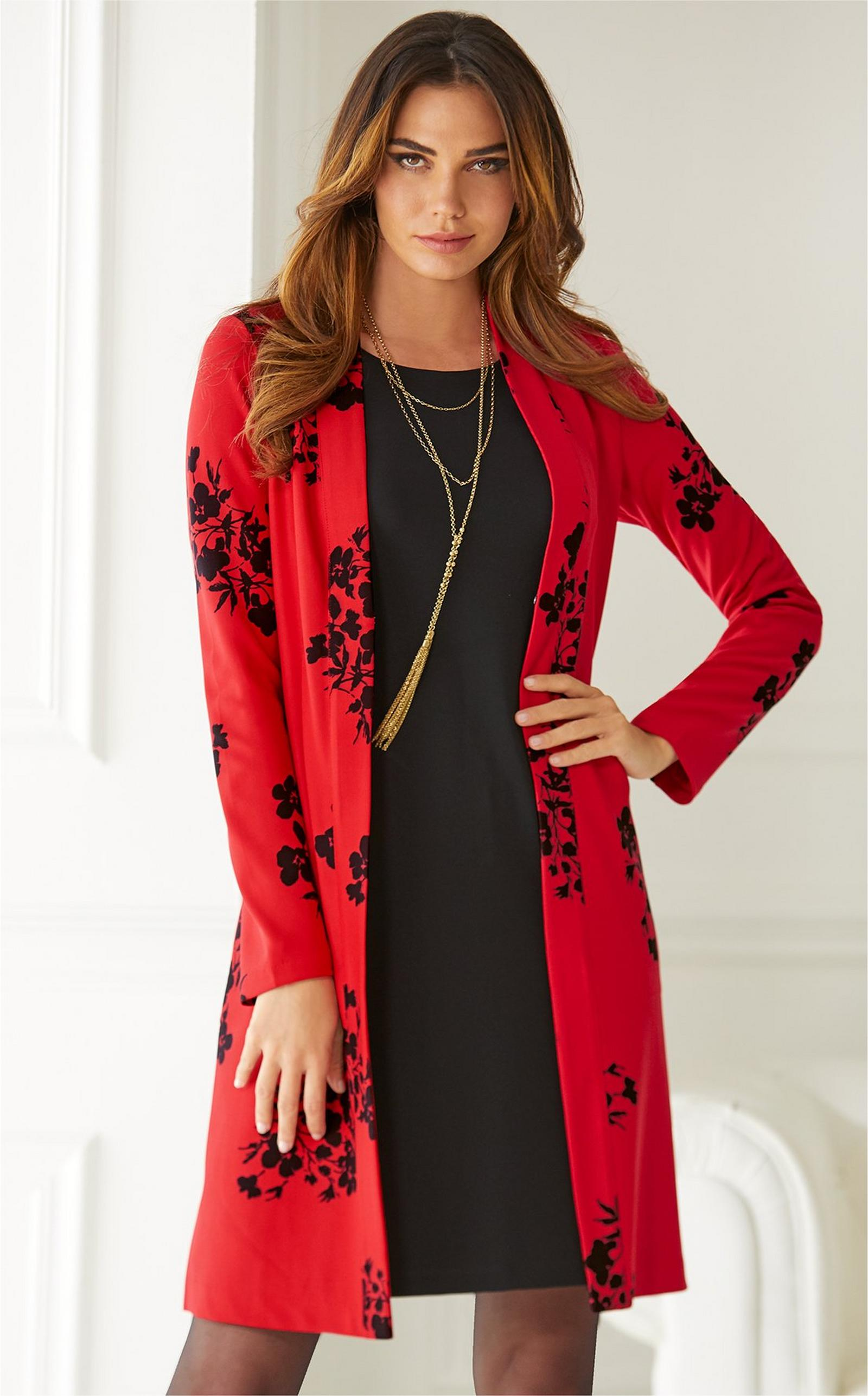 model wearing red floral cardigan over black trapeze dress and sheer black tights.