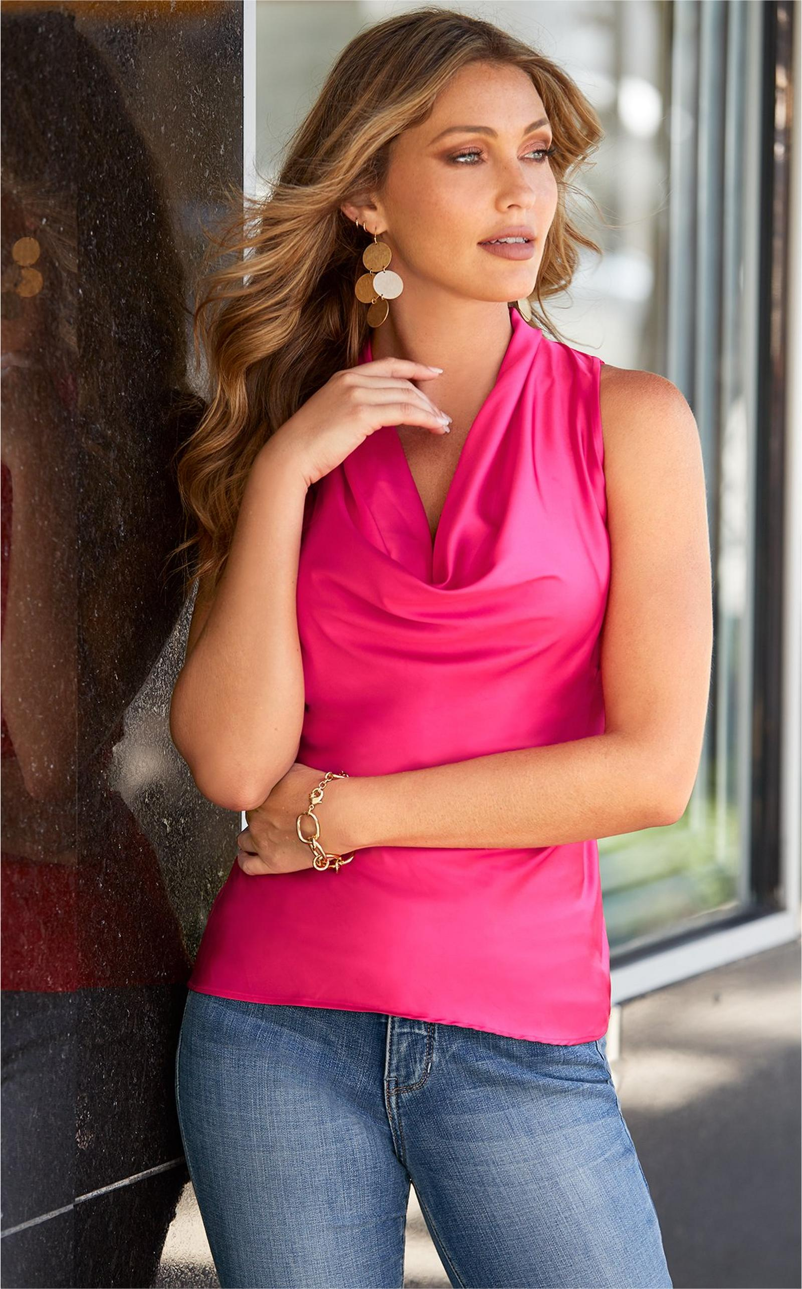 model wearing hot pink cowl neck tank top with light jeans and gold earrings.