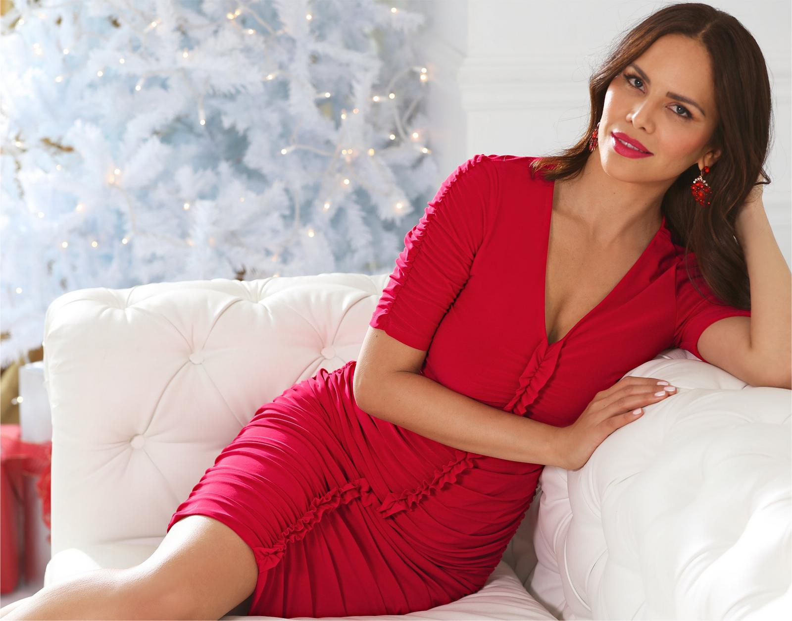 model laying on white couch with white christmas tree in background wearing a red ruched dress and red earrings.
