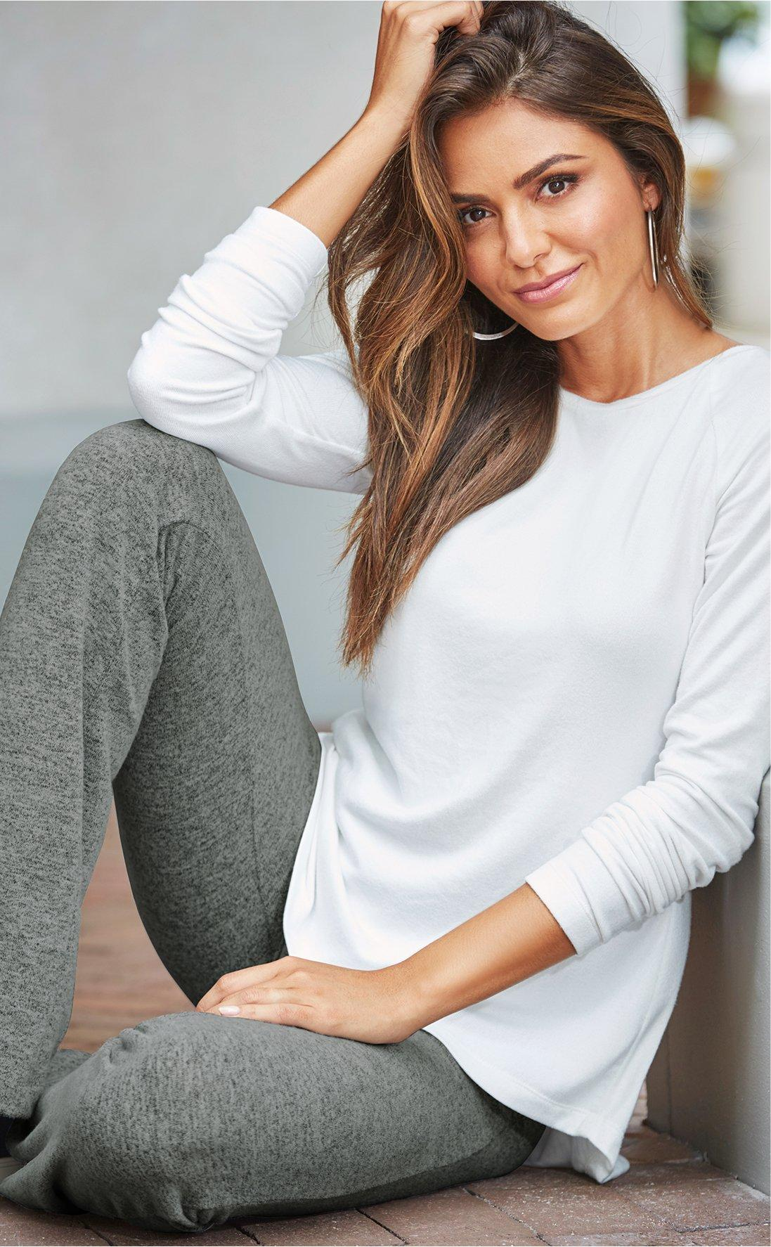 model wearing white sweater over gray yoga pants.
