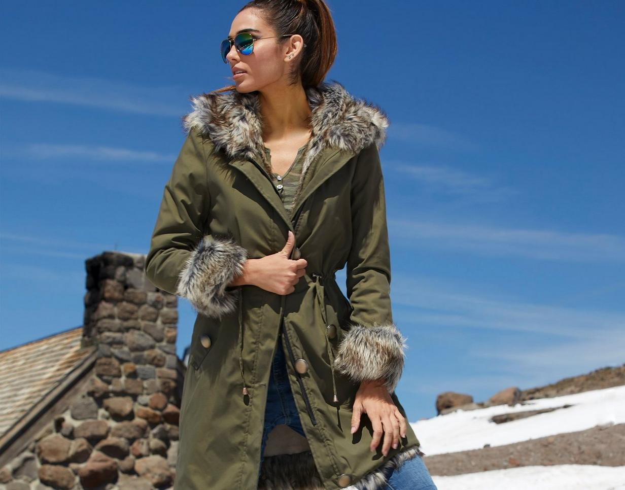 model wearing army green coat with faux fur lining and camouflage tank top, mirrored aviator sunglasses, and jeans.