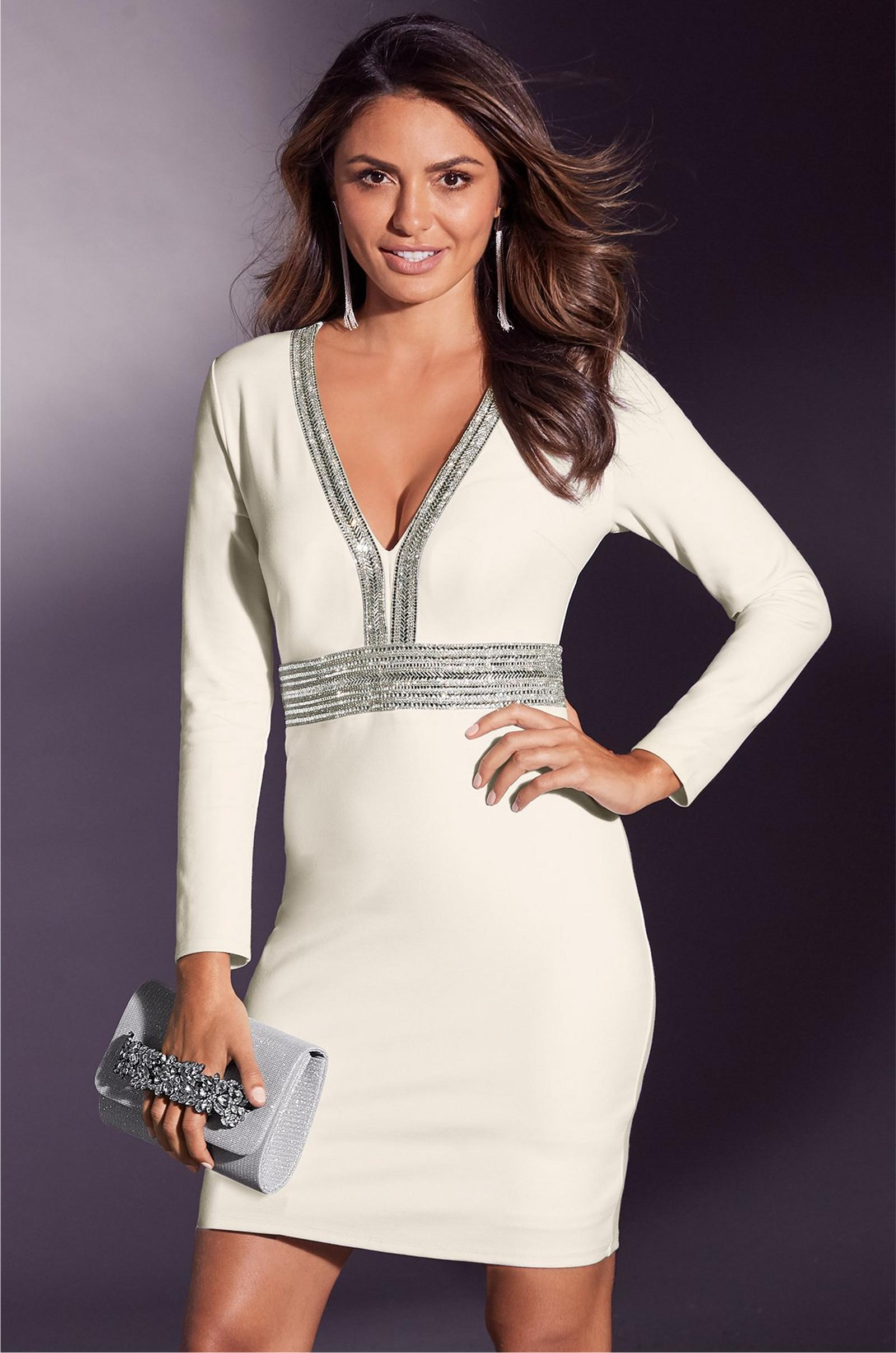 model wearing white long sleeve cocktail dress with silver embellishments while holding a silver holiday clutch.