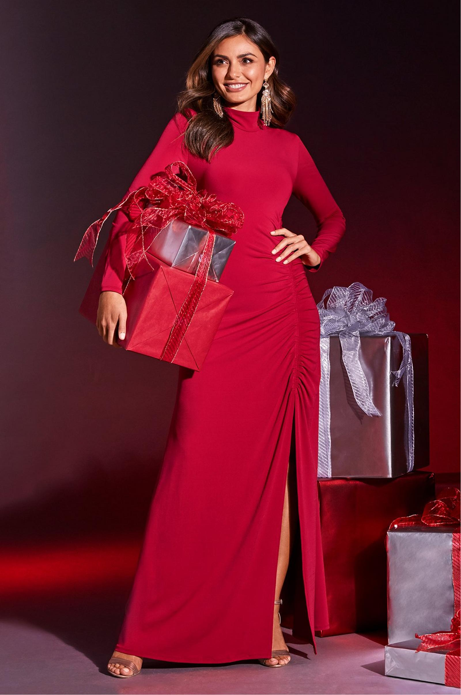 model wearing long sleeve mock neck gown in red while holding wrapped gifts.