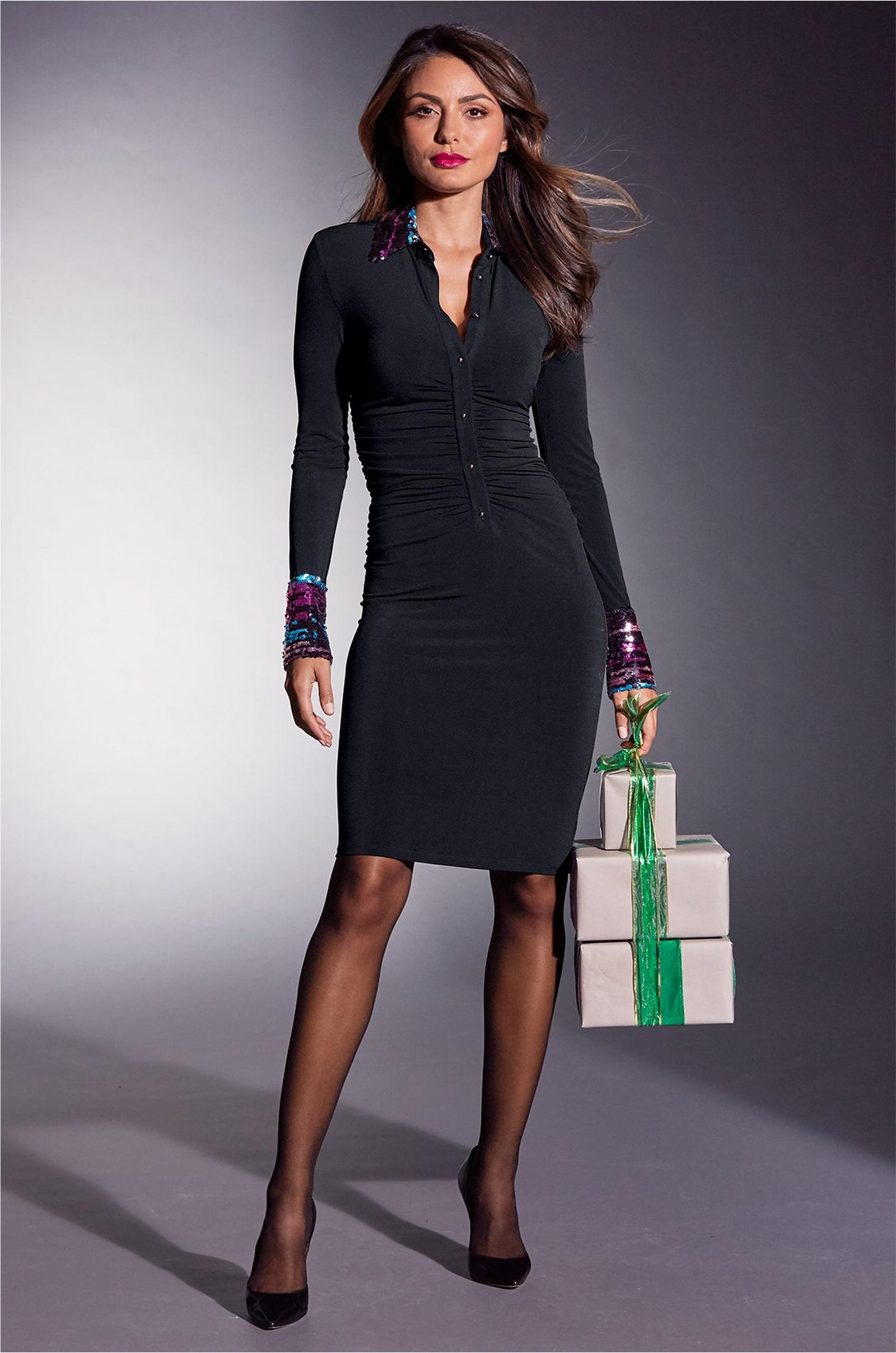 model wearing a black dress with sequined collar and cuffs while holding wrapped gifts.