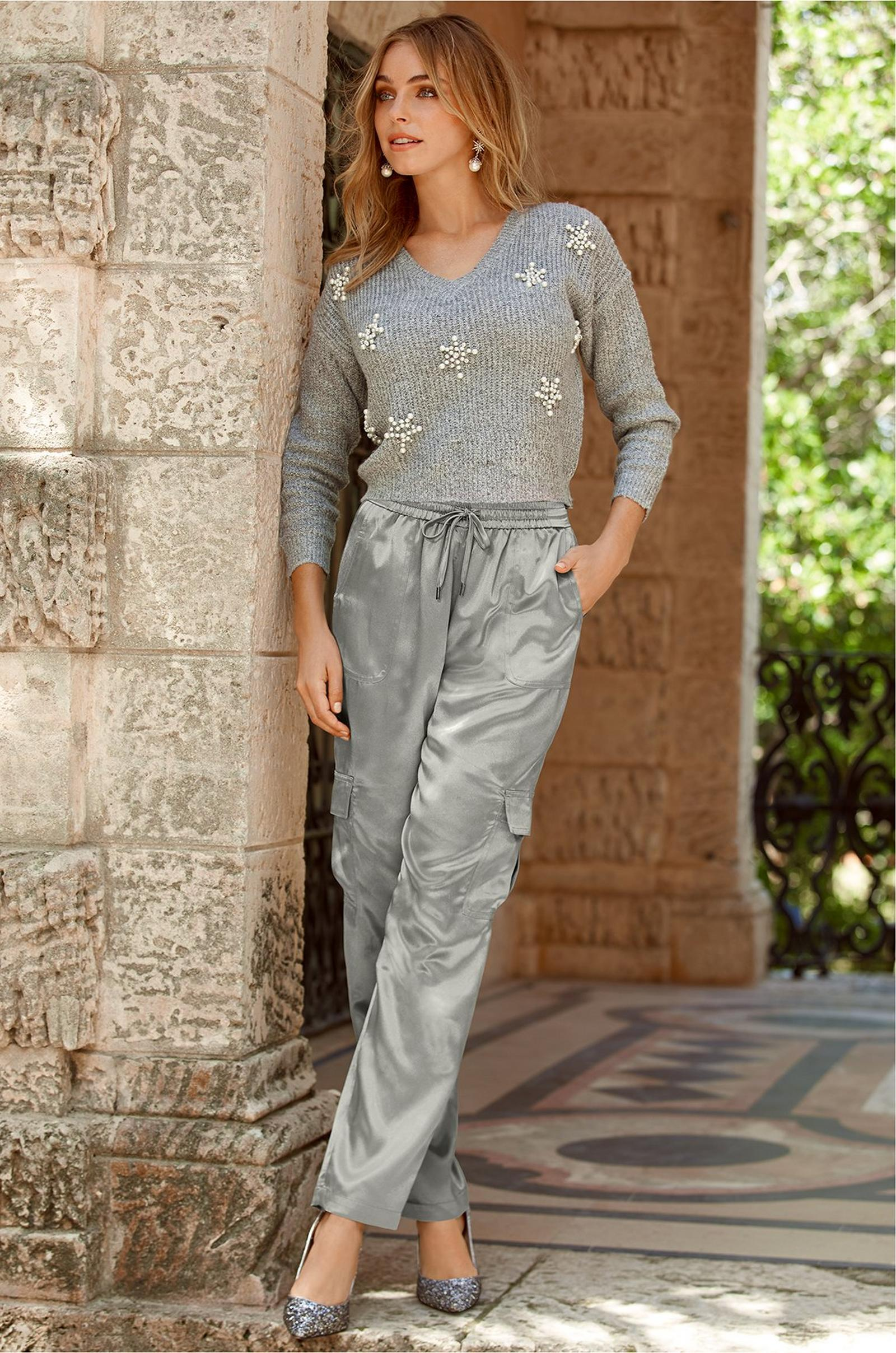 model wearing gray crop sweater with snowflake embellishments with silver metallic cargo pants and sequin pumps.