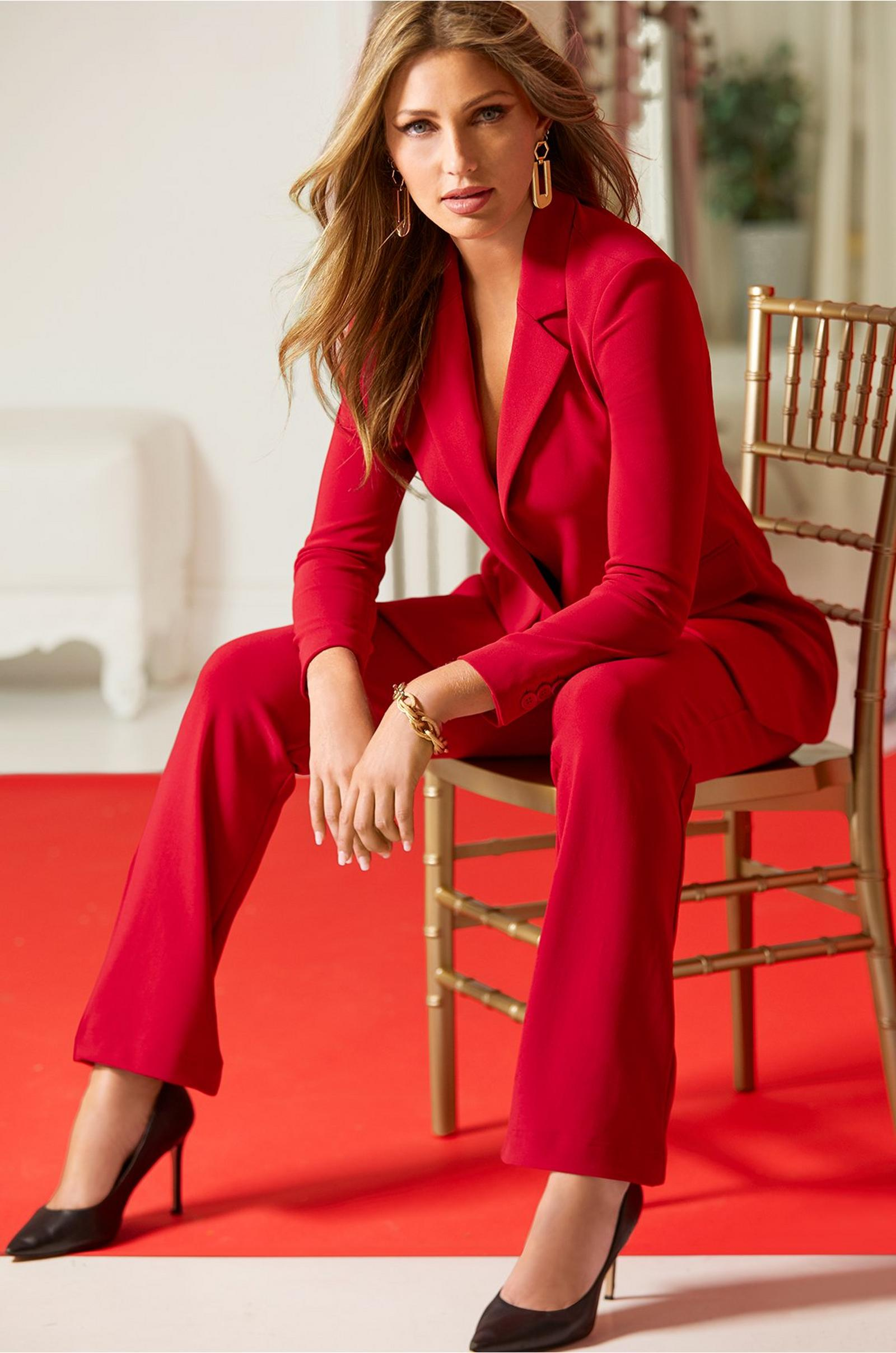 model sitting in a wood chair wearing a red blazer and red travel pants with black pumps.