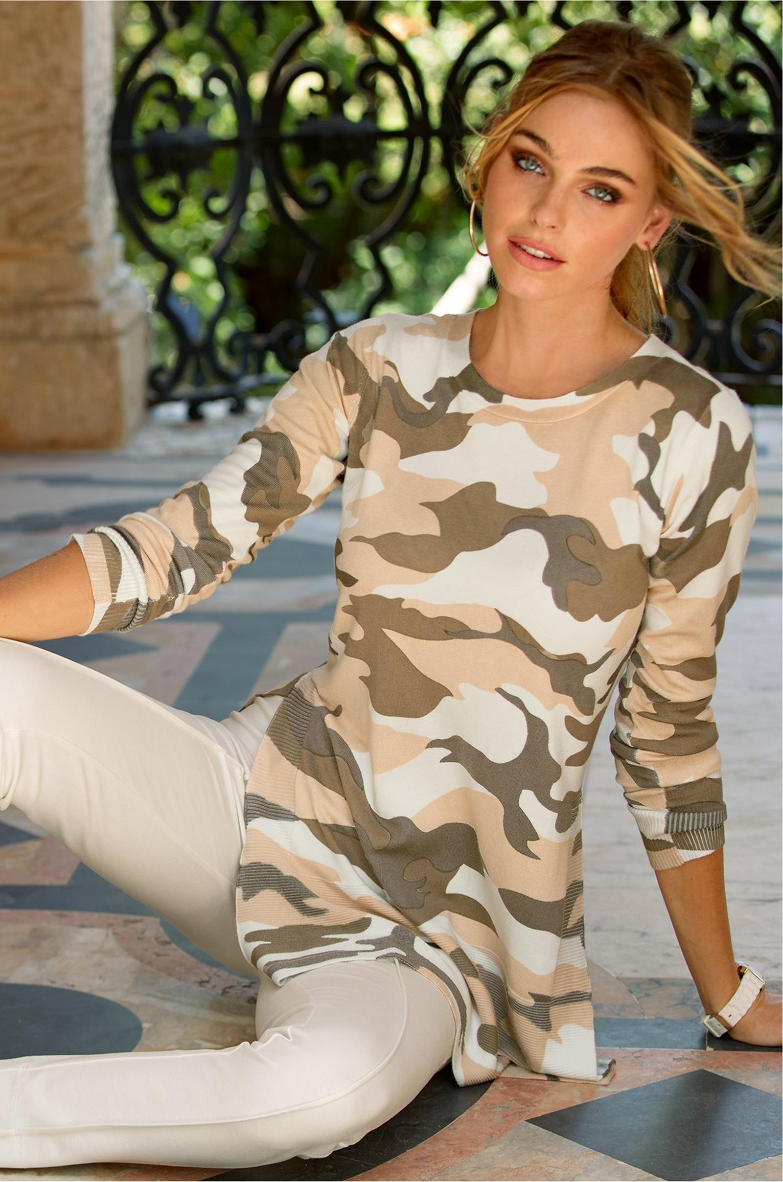 model lounging in a camouflage tunic sweater and white ponte leggings.