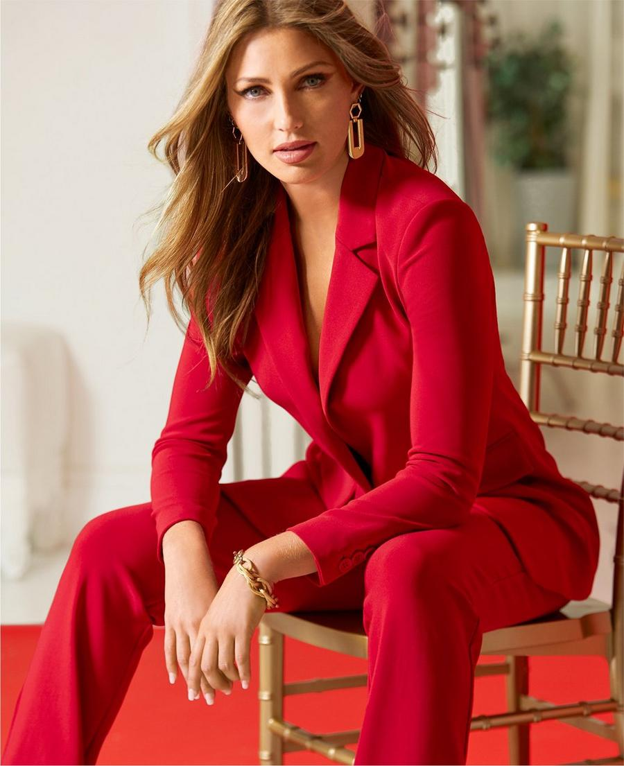 model sitting on a wooden chair wearing a red blazer with red travel pants