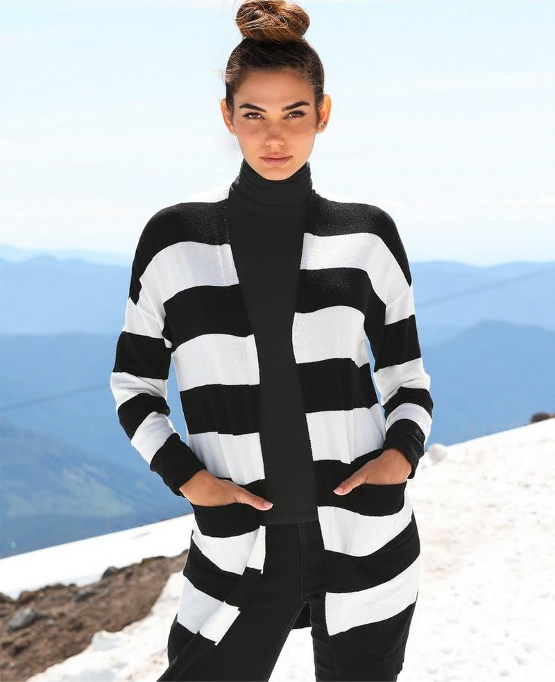 model wearing a black and white striped cardigan over a black turtleneck and black leggings.