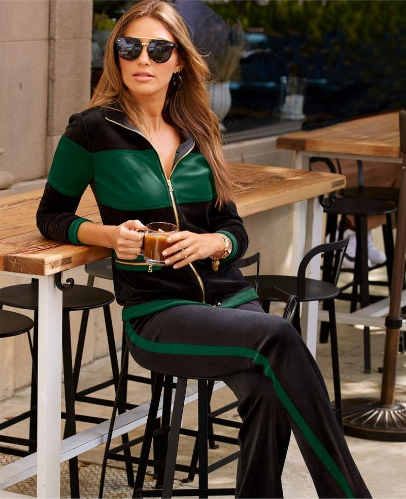 model wearing green and black warm-up with gold zipper.