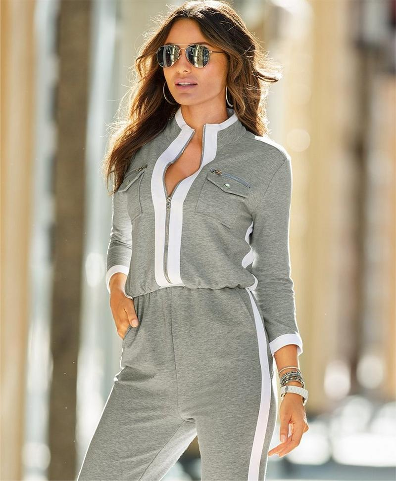 model wearing gray sports jumpsuit with white piping.