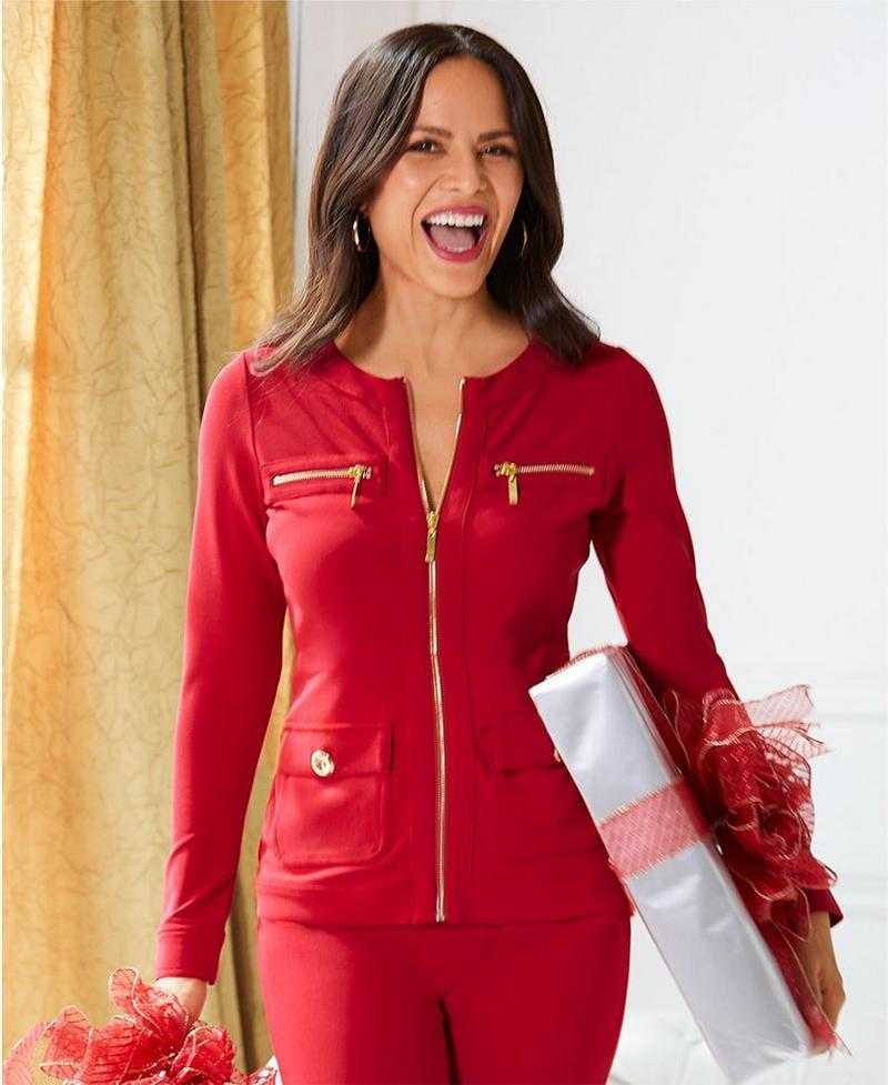 model wearing red travel coordinates with gold zippers.