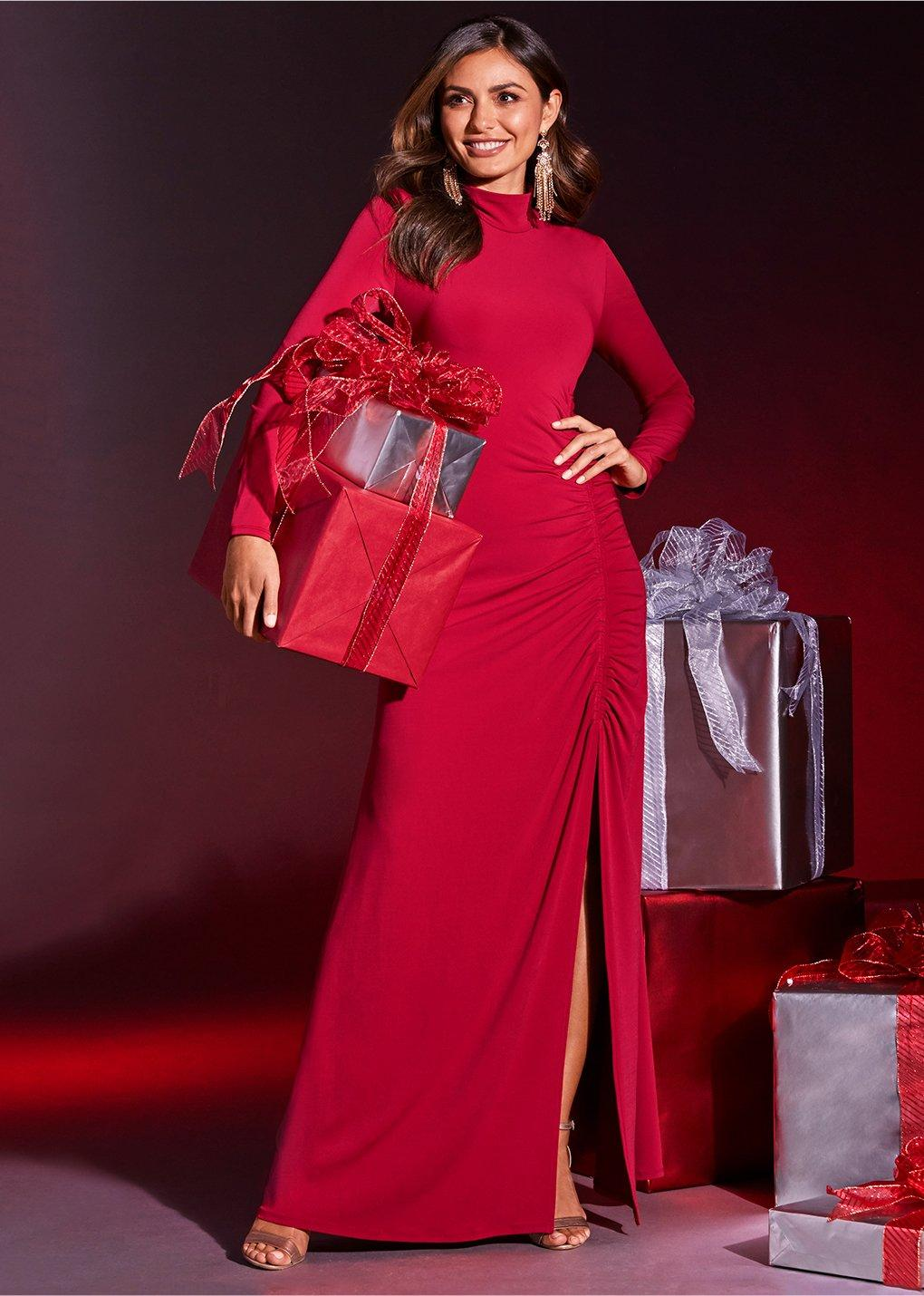 model wearing long sleeve mock neck red gown while holding wrapped gifts.