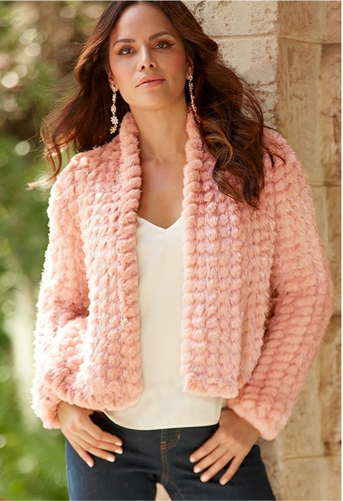 model wearing blush sparkly faux fur jacket over white tank top and jeans.