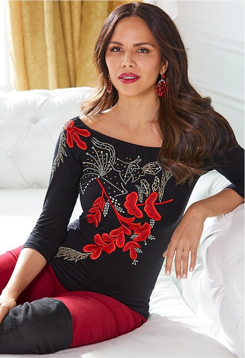 model wearing off-the-shoulder black top with a red embroidered design