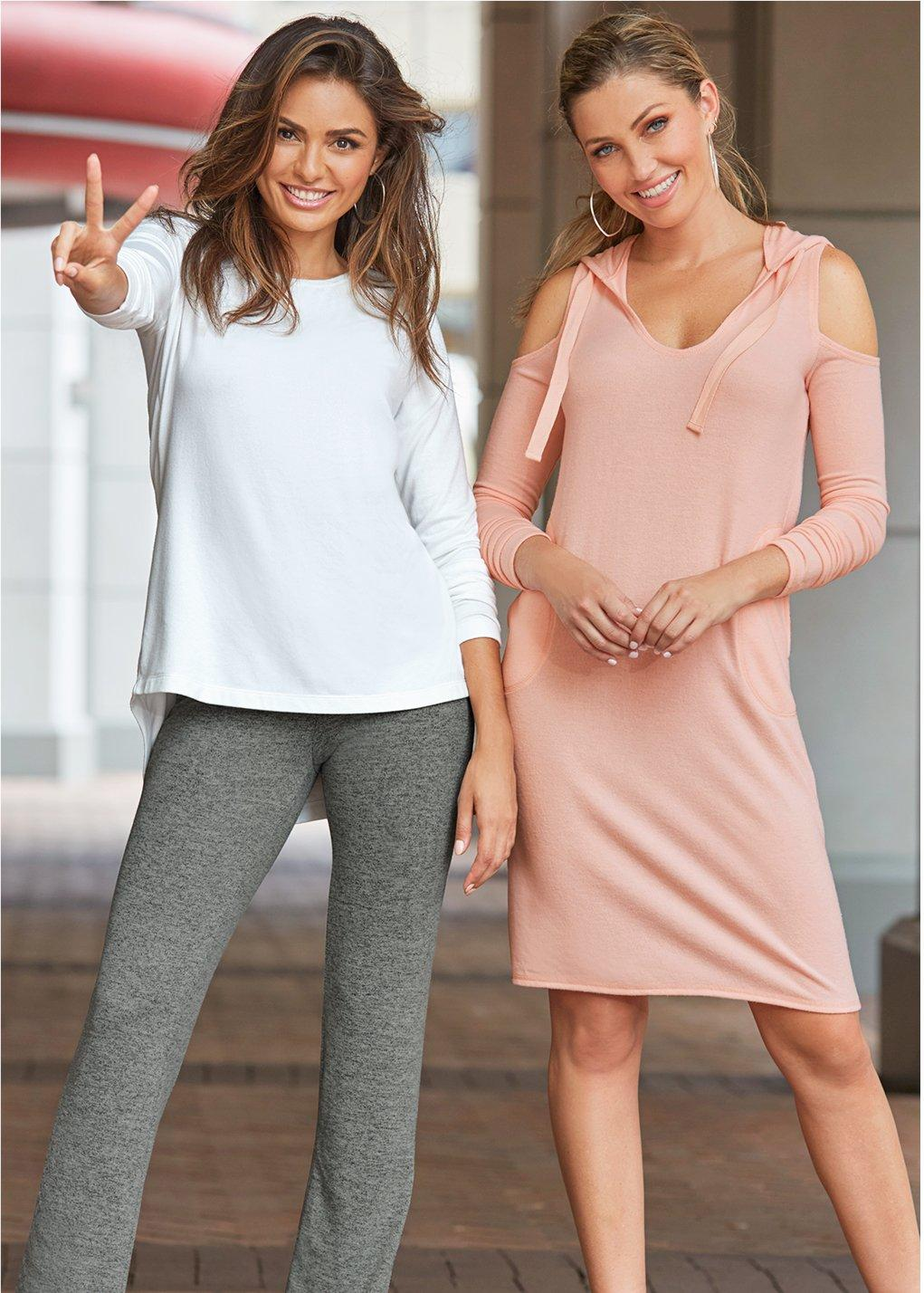 left: model wearing white sweater over gray yoga pants and holding up the peace sign. right: model wearing pink hooded cold-shoulder sports dress.