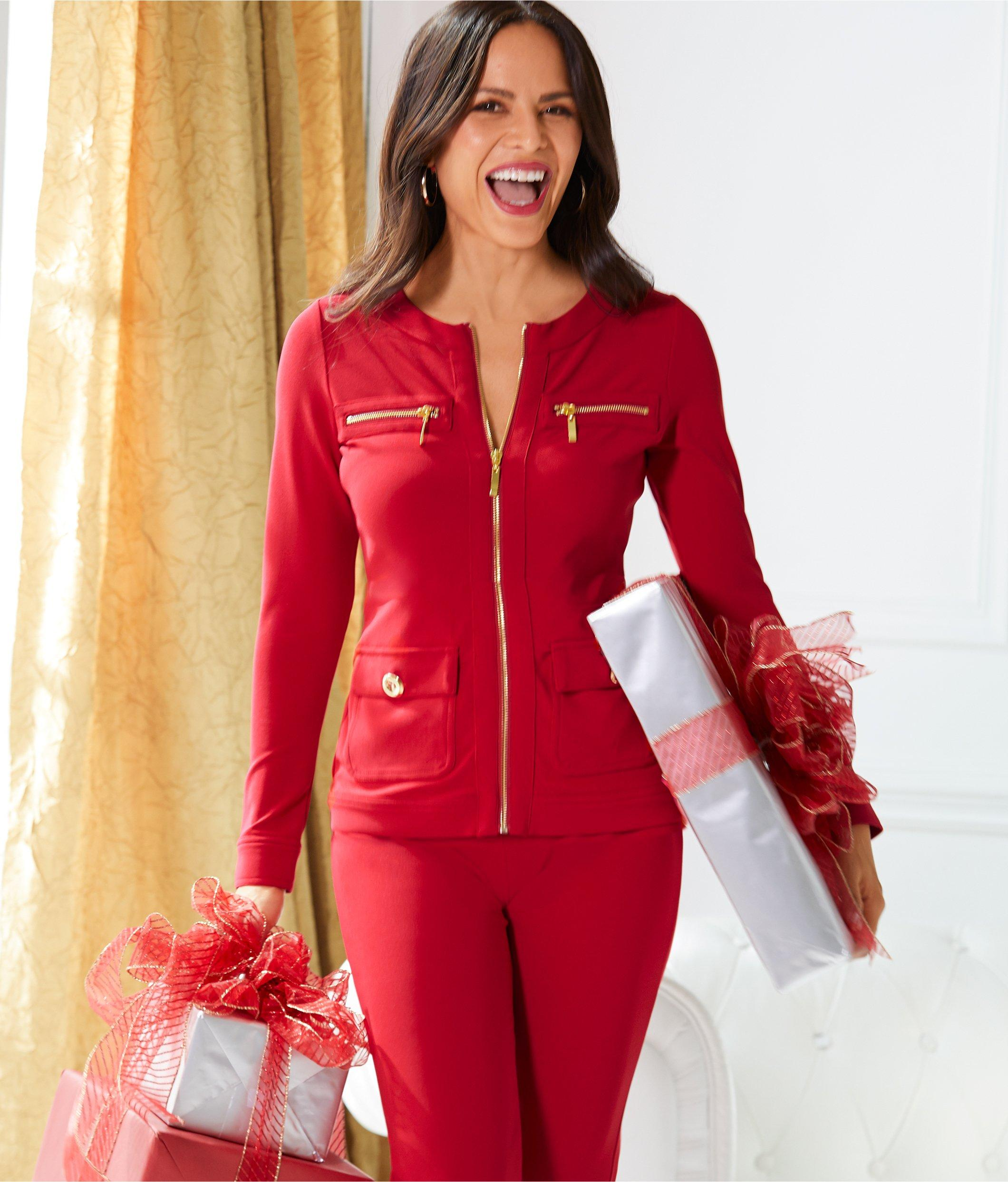 model wearing red travel coordinates while holding wrapped gifts.