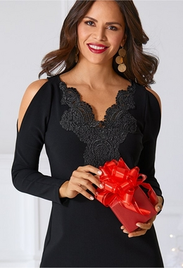 model wearing cold-shoulder black travel top with lace detail while holding a wrapped red gift