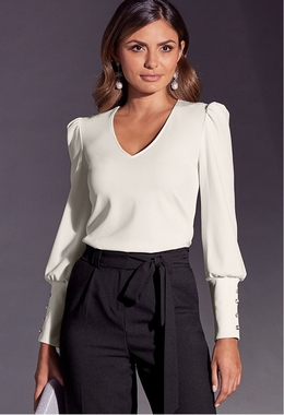 model wearing a white v-neck, long-sleeve top with black tie waist pants